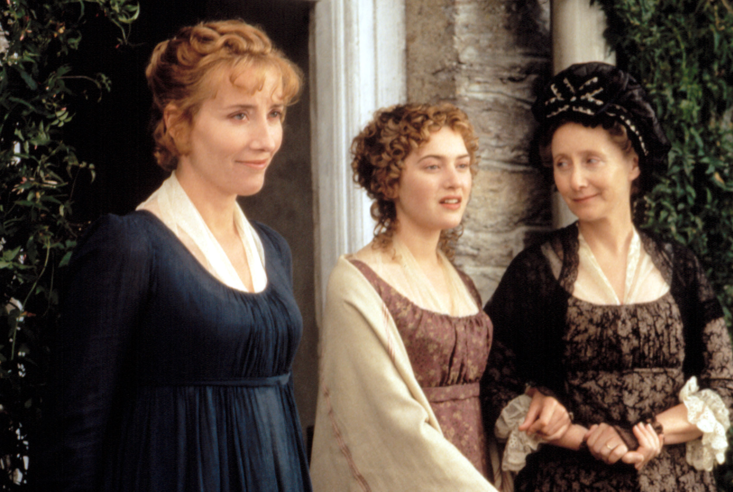 Emma Thompson, Kate Winslet, and Gemma Jones stand outside a house in regency clothes