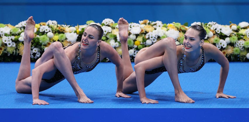 The synchronized swimmers each have a leg twisted over an arm as they crouch on the ground