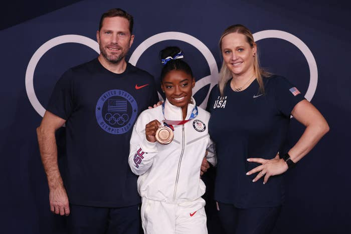 Simone posing with her coaches for a photo and holding up her bronze medal