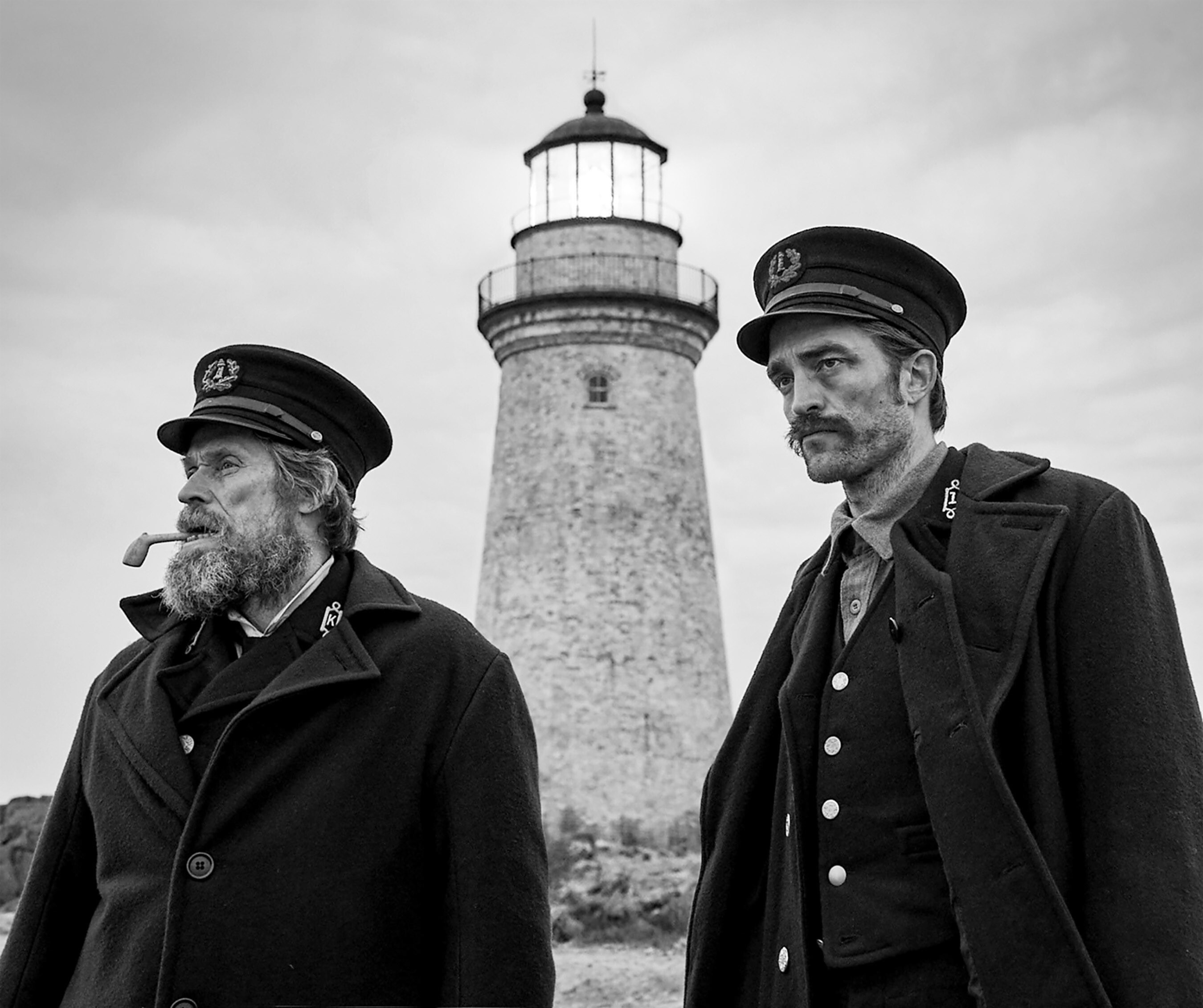 Willem Dafoe and Robert Pattison stand outside a lighthouse