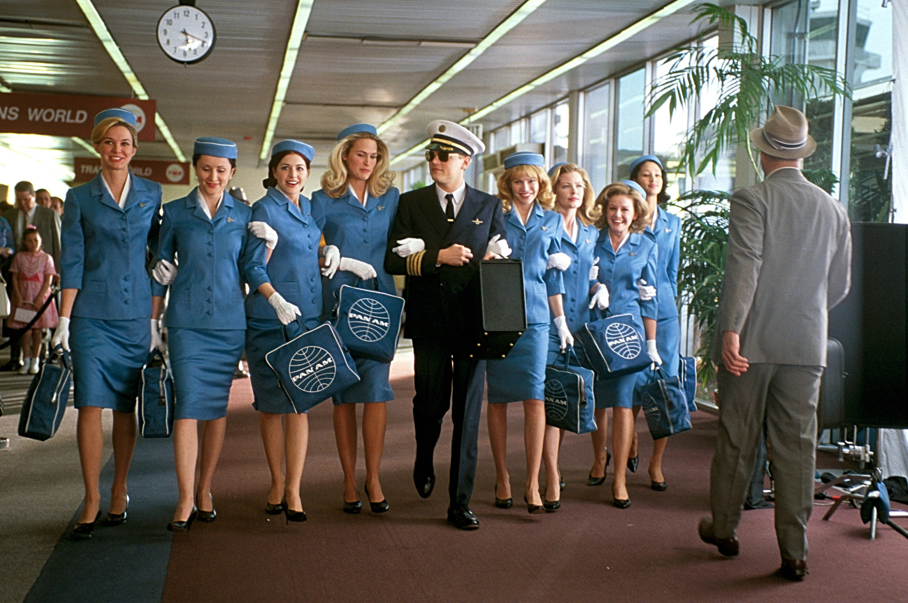 Leonardo Di Caprio walks through an airport with a whole group of flight attendants on his arm