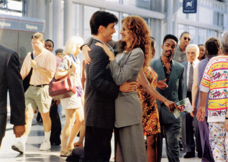 Rupert Everett and Julia Roberts embrace in an airport