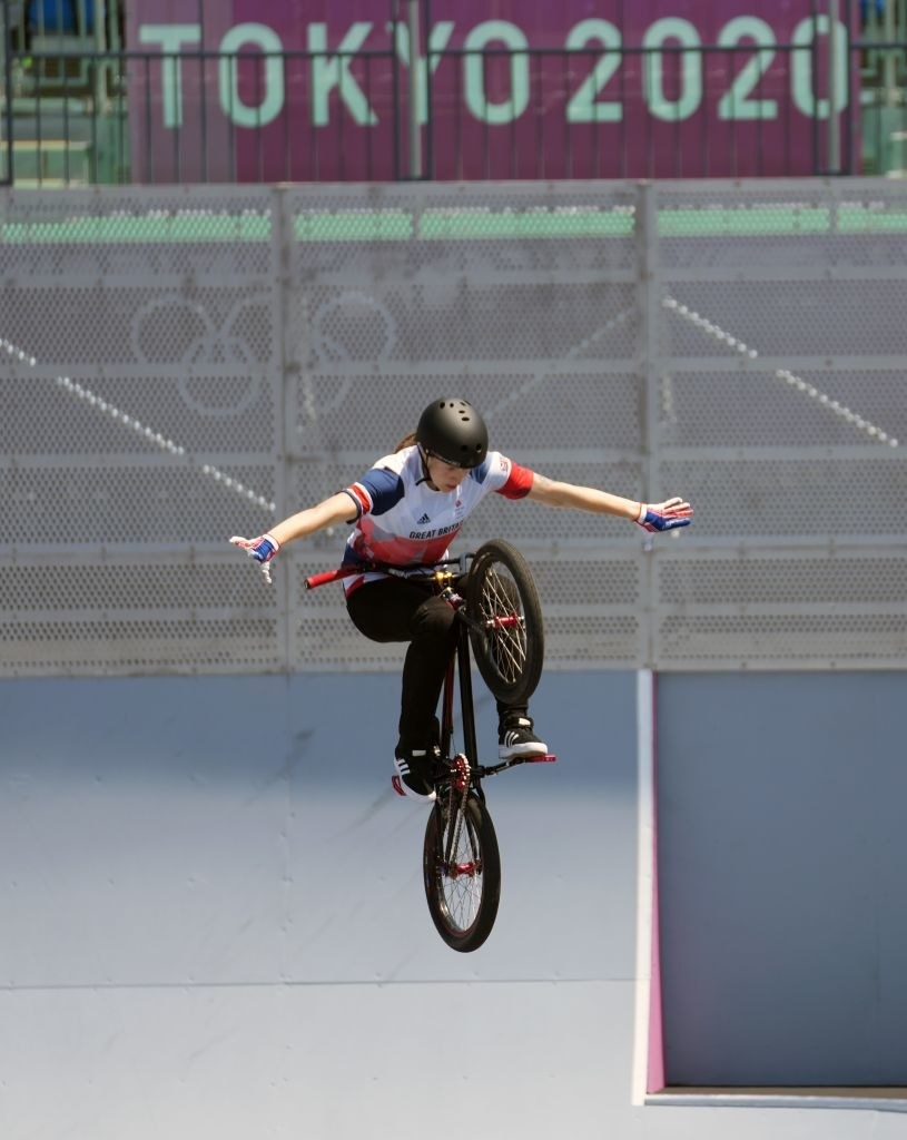 An athlete is mid-air on their bike without touching the handles