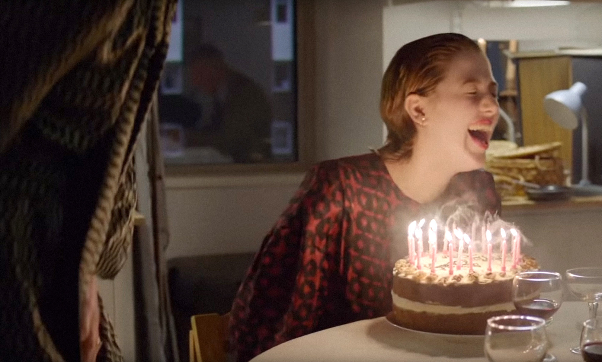 Honor Swinton Byrne laughs with a birthday cake in front of her