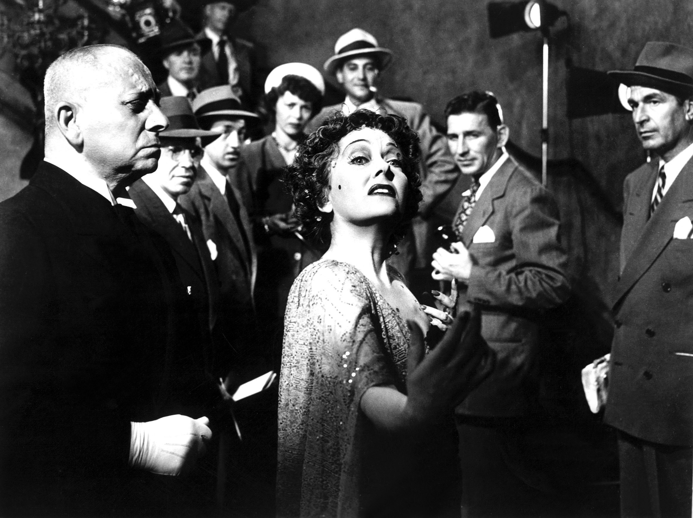 Gloria Swanson descends a staircase full of people