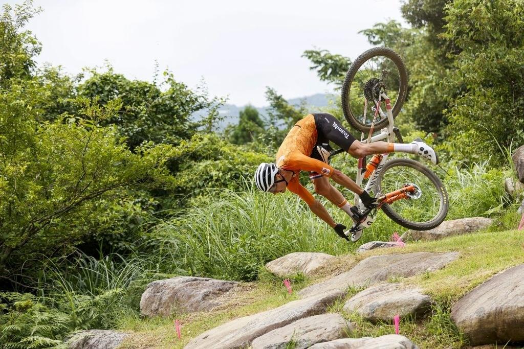 The mountain biker tilting forward while he's mid-air