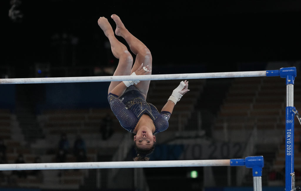 Suni Lee focused on the bar as she's upside down in mid-air