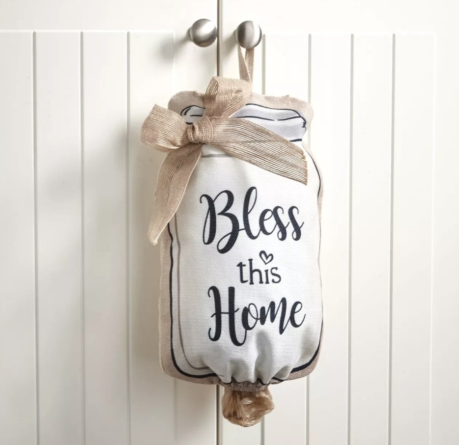 """A mason jar-looking bag holder that reads """"Bless this Home"""" hanging off a hook"""