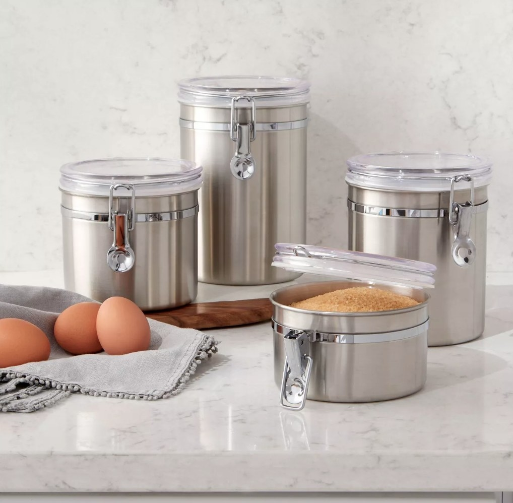 A set of 4 uniquely sized stainless stell canisters filled with food