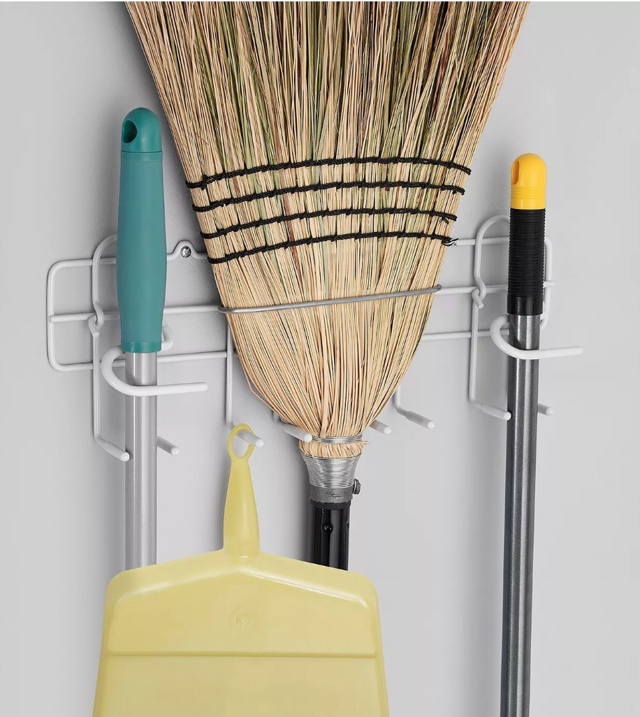 the rack, which mounts to the wall and holds mops and brooms