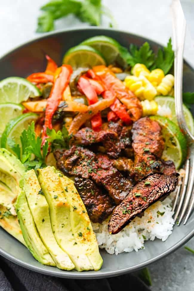 A rice bowl with steak, avocado, and bell pepper.
