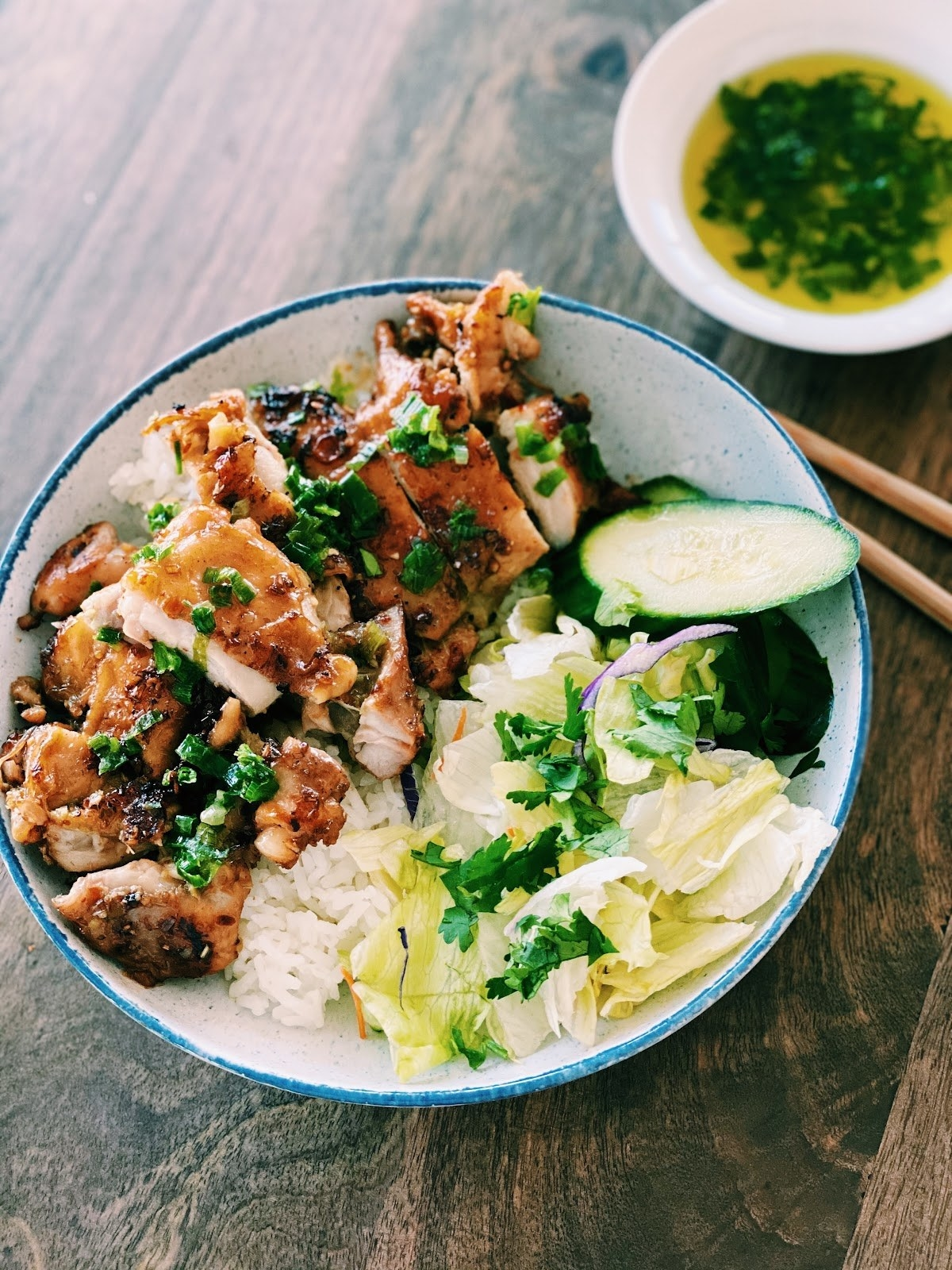 A rice bowl with chicken, cabbage, and scallion oil.