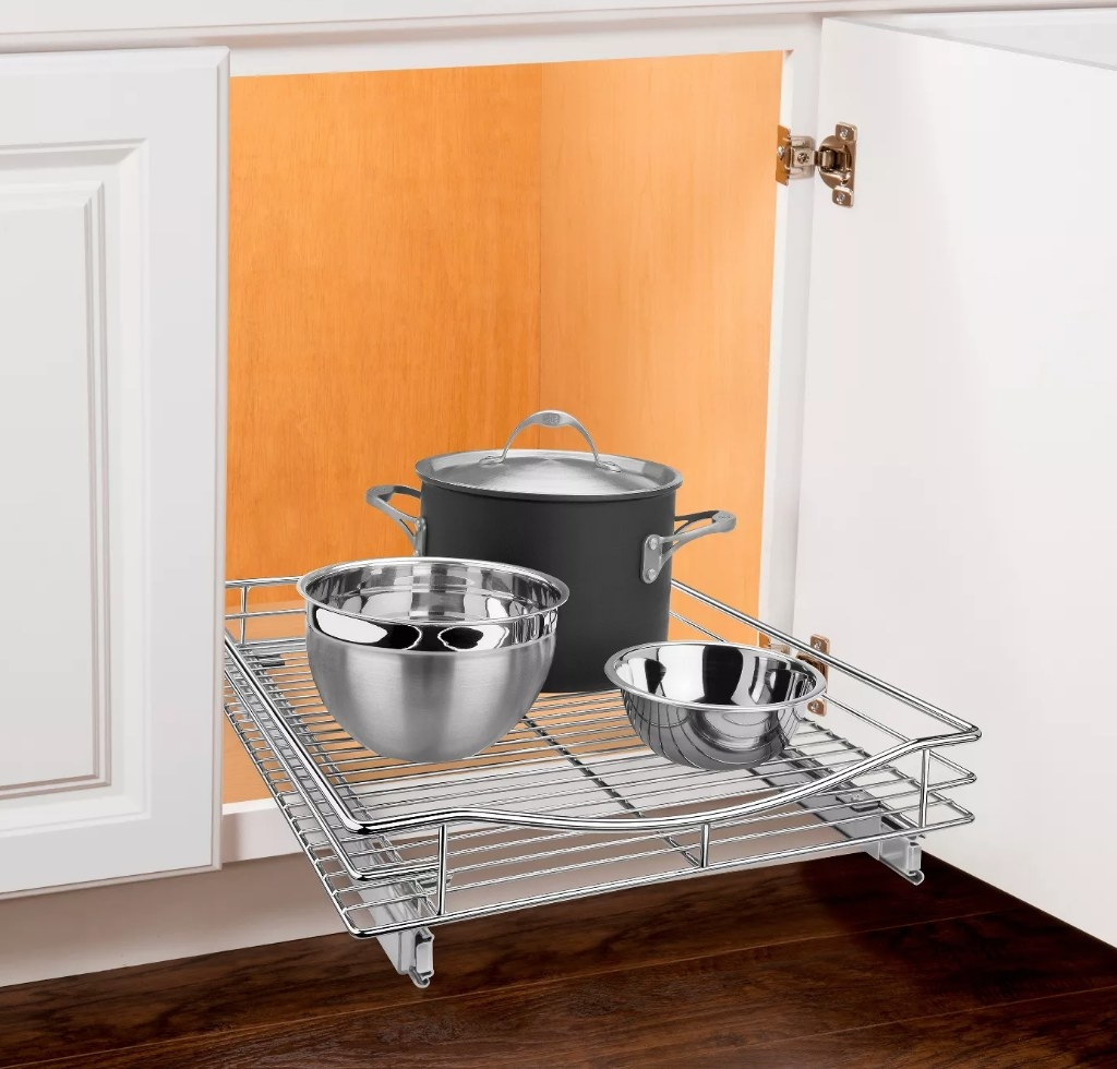 A slide out, cabinet organizer stacked with a pot and two mixing bowls in a cabinet