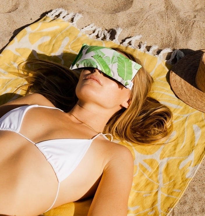 Someone snoozing on the beach while using the eye pillow on their face