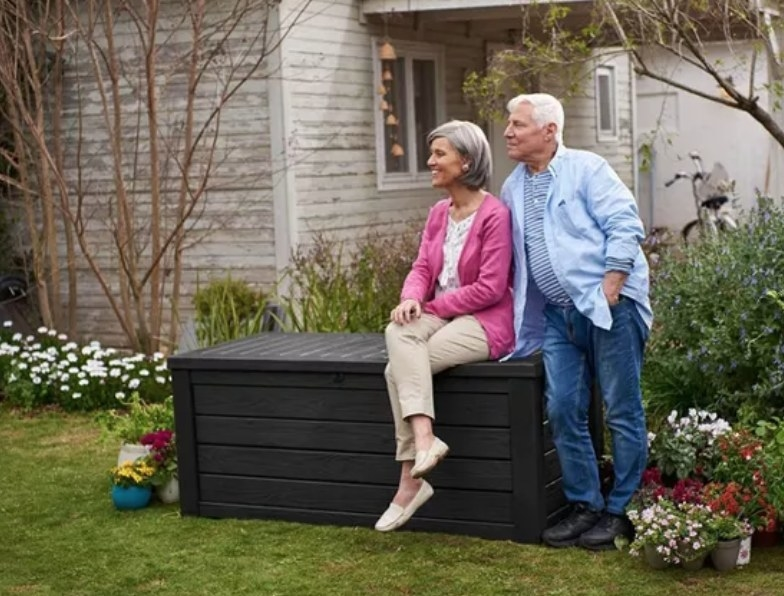 A dark gray, resin outdoor storage box with a model sitting atop in a garden
