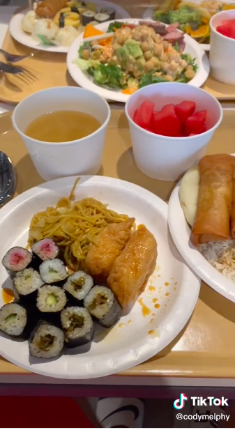 Several plates of food that includes sushi, noodles, and fruit