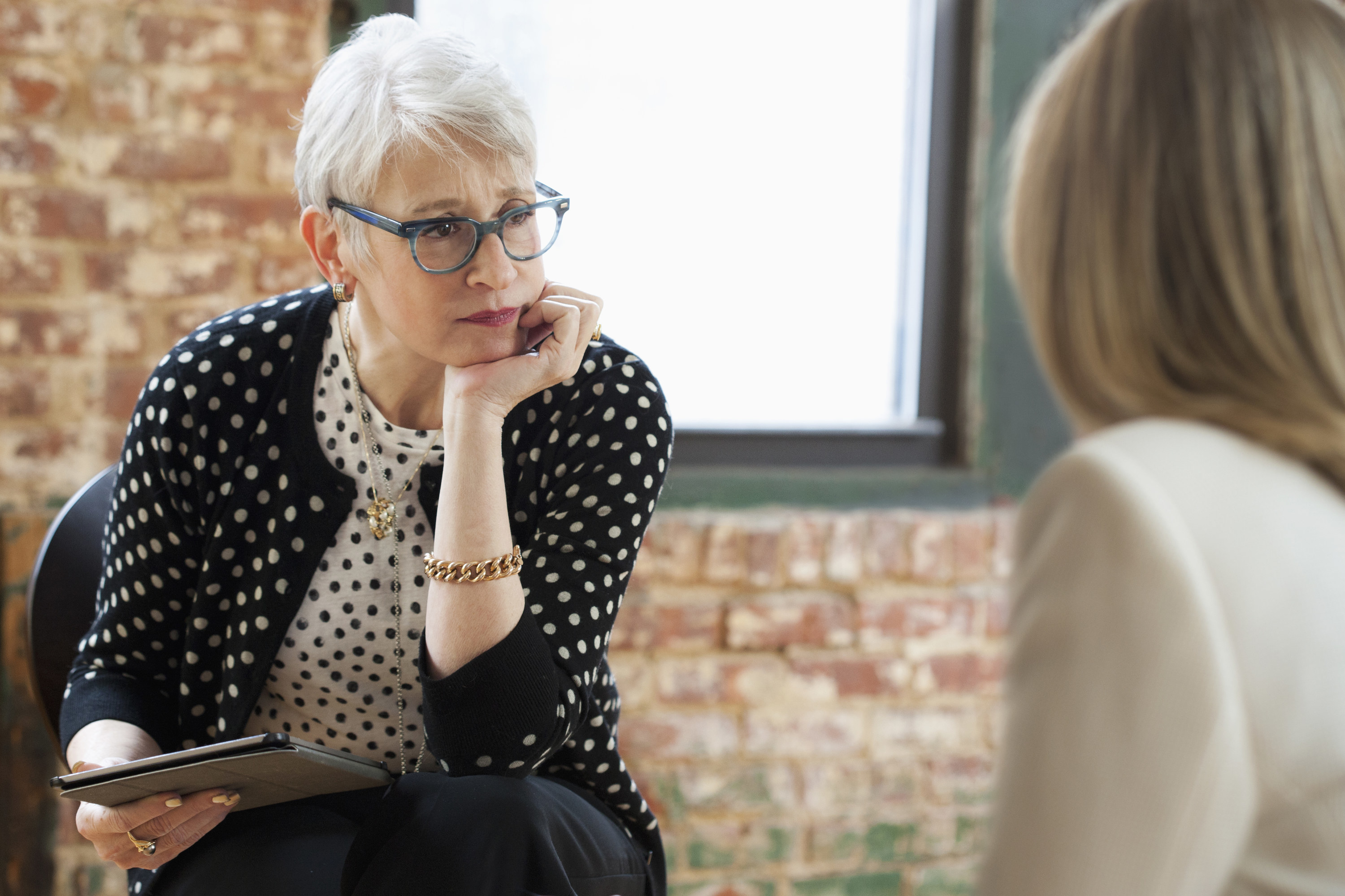 A therapist sits on a chair with a note pad and her head on her palm as she listens to a client