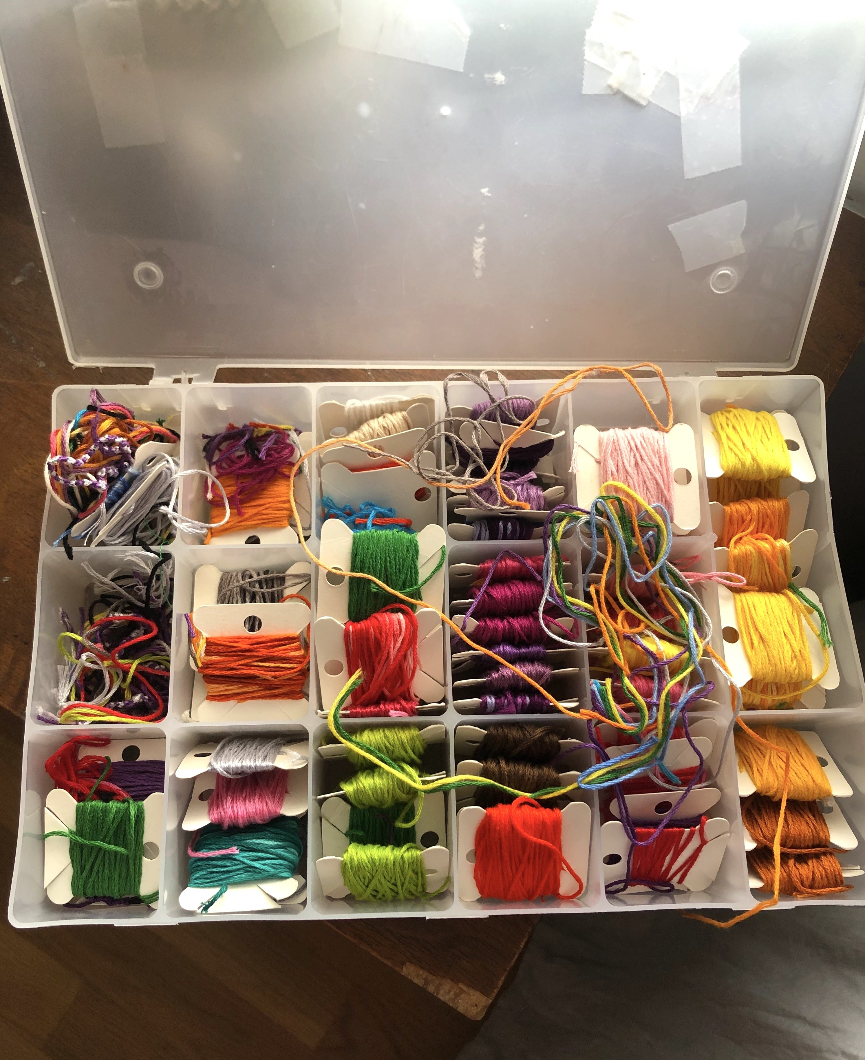 Rolls of colorful string wrapped around paper squares in a plastic box