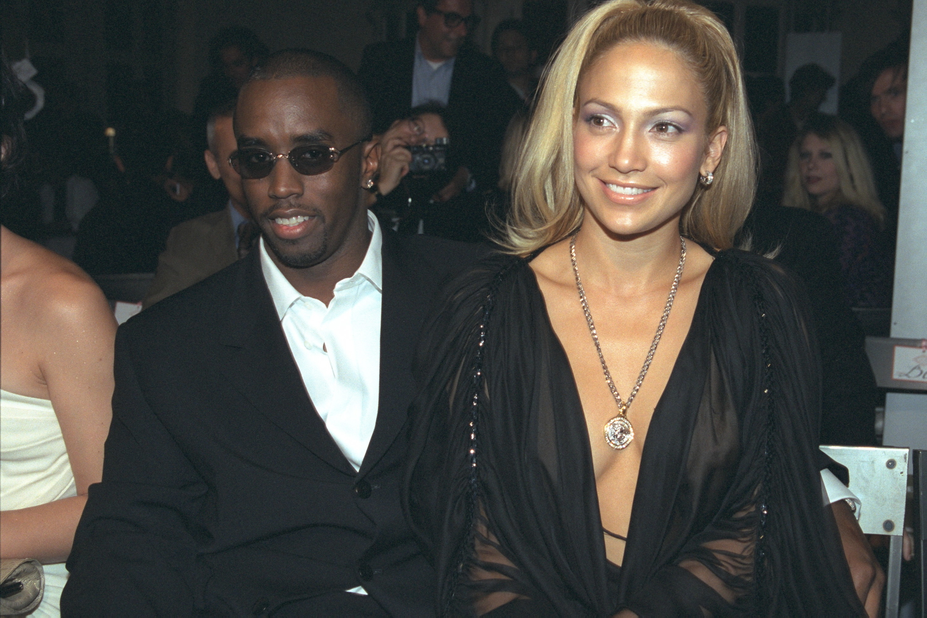 Jennifer and Diddy smile while sitting close together at an event