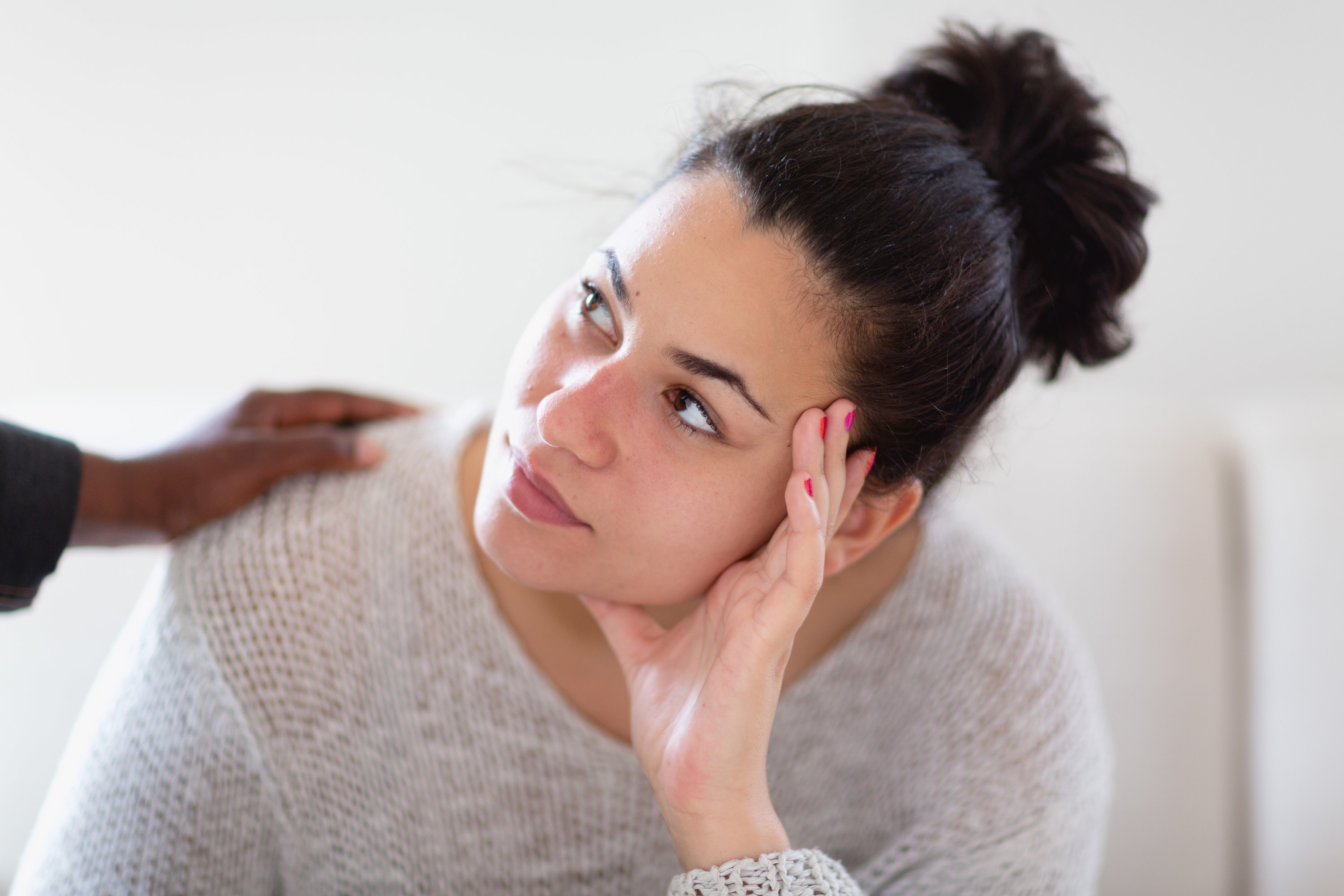Young Hispanic woman looking up to the person who is putting a hand on her shoulder, could be support, mentoring, consoling in psychotherapy or friendship