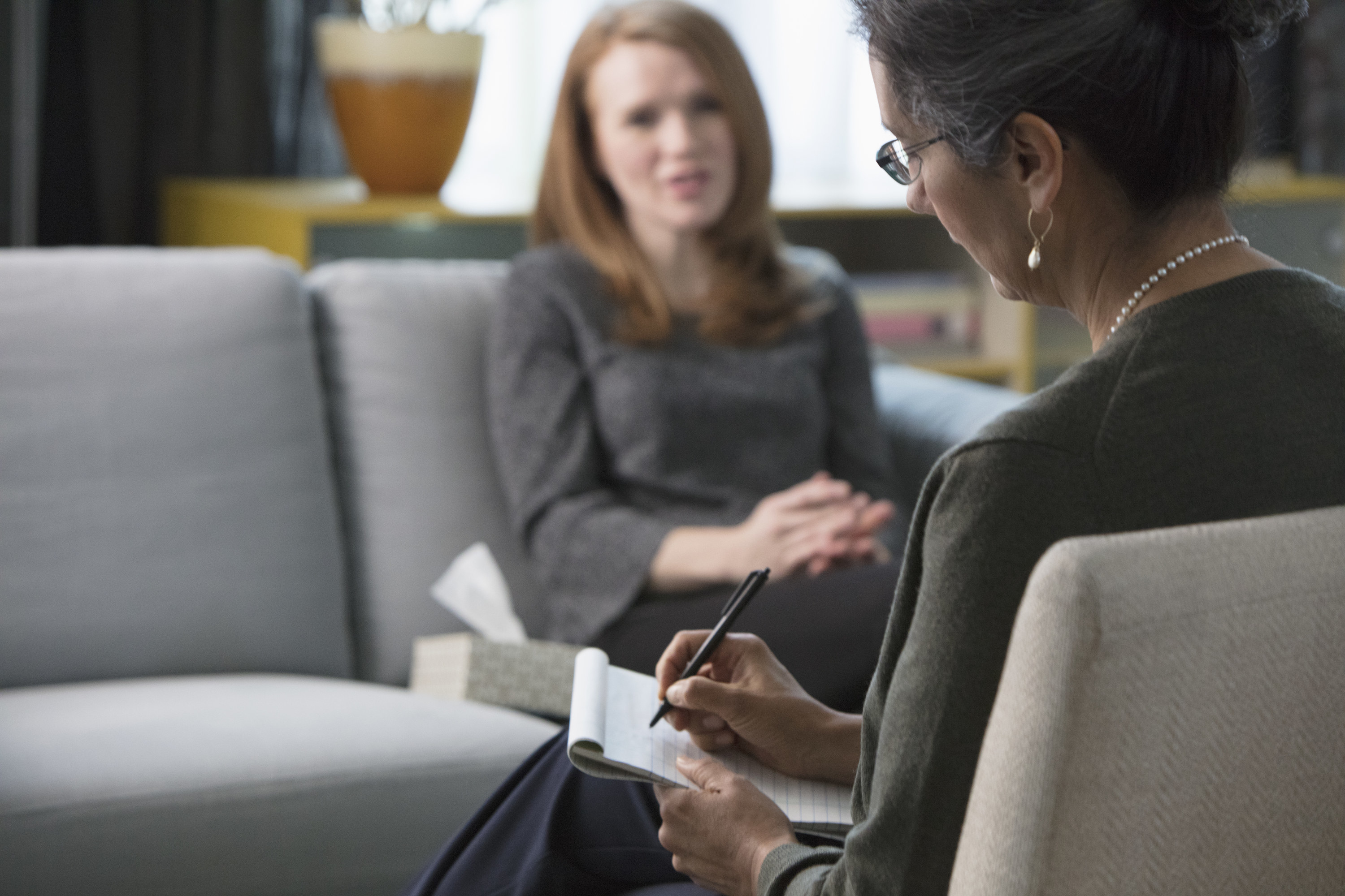 Woman speaks to her therapist, who is taking notes