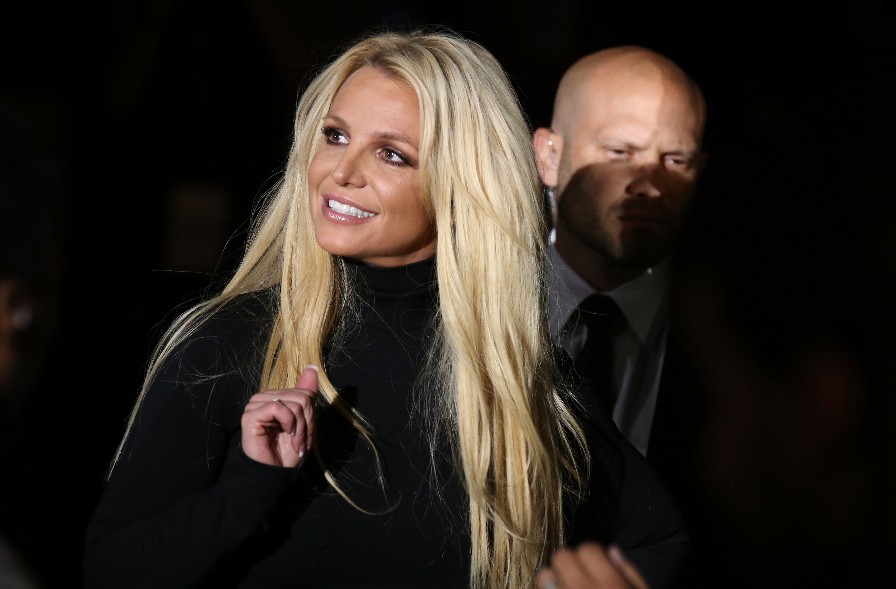 Britney smiles and waves at an event