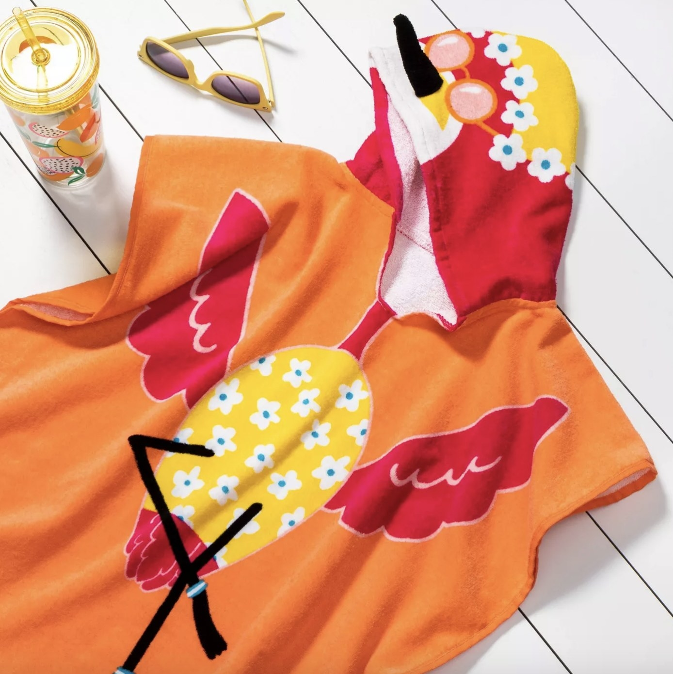 The orange hooded towel has a red flamingo wearing sunglasses and yellow floral clothing