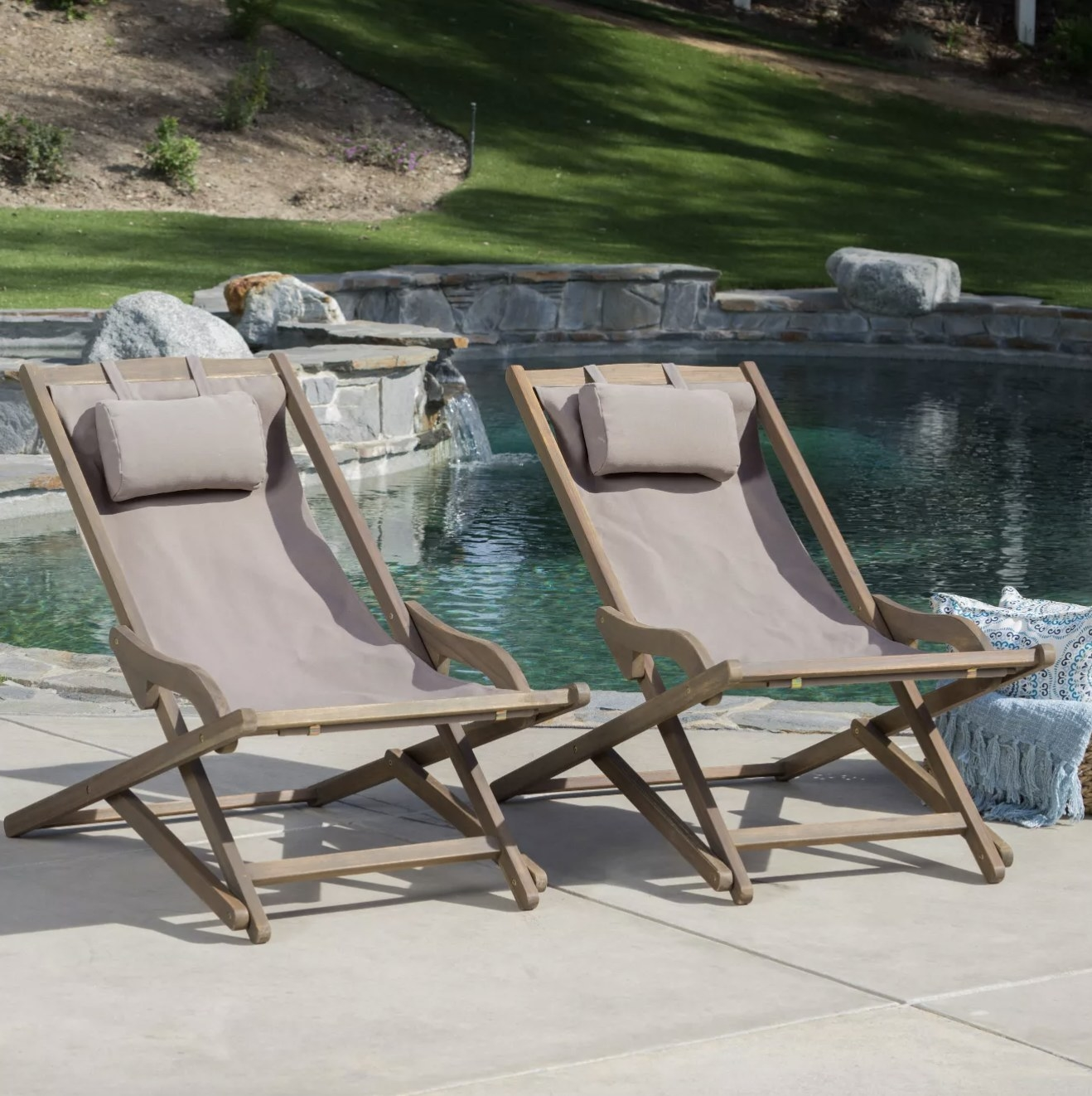 The taupe sling chairs are a mix of fabric and wood are outside near water
