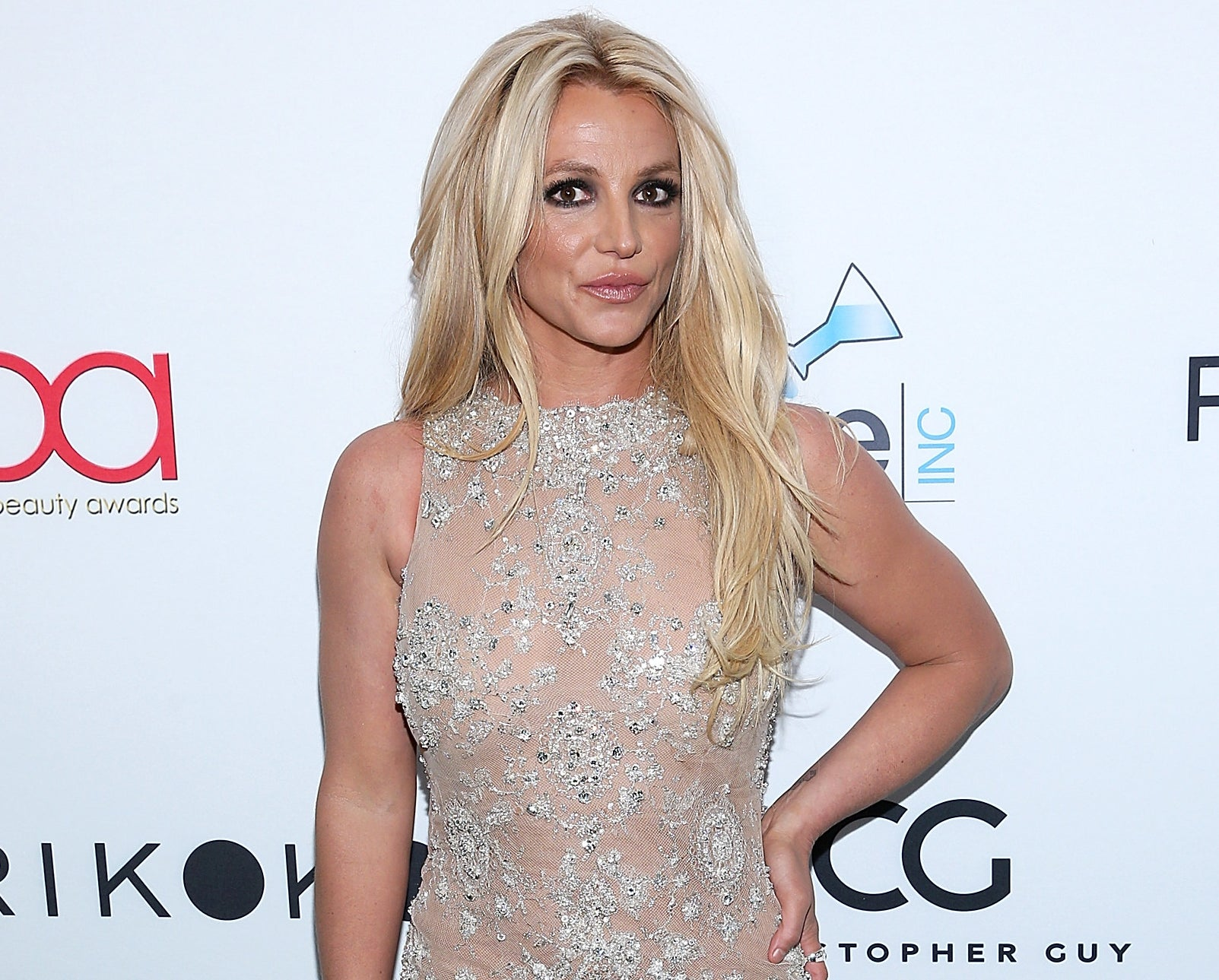 Britney wears a nude dress with diamonds while posing on a red carpet