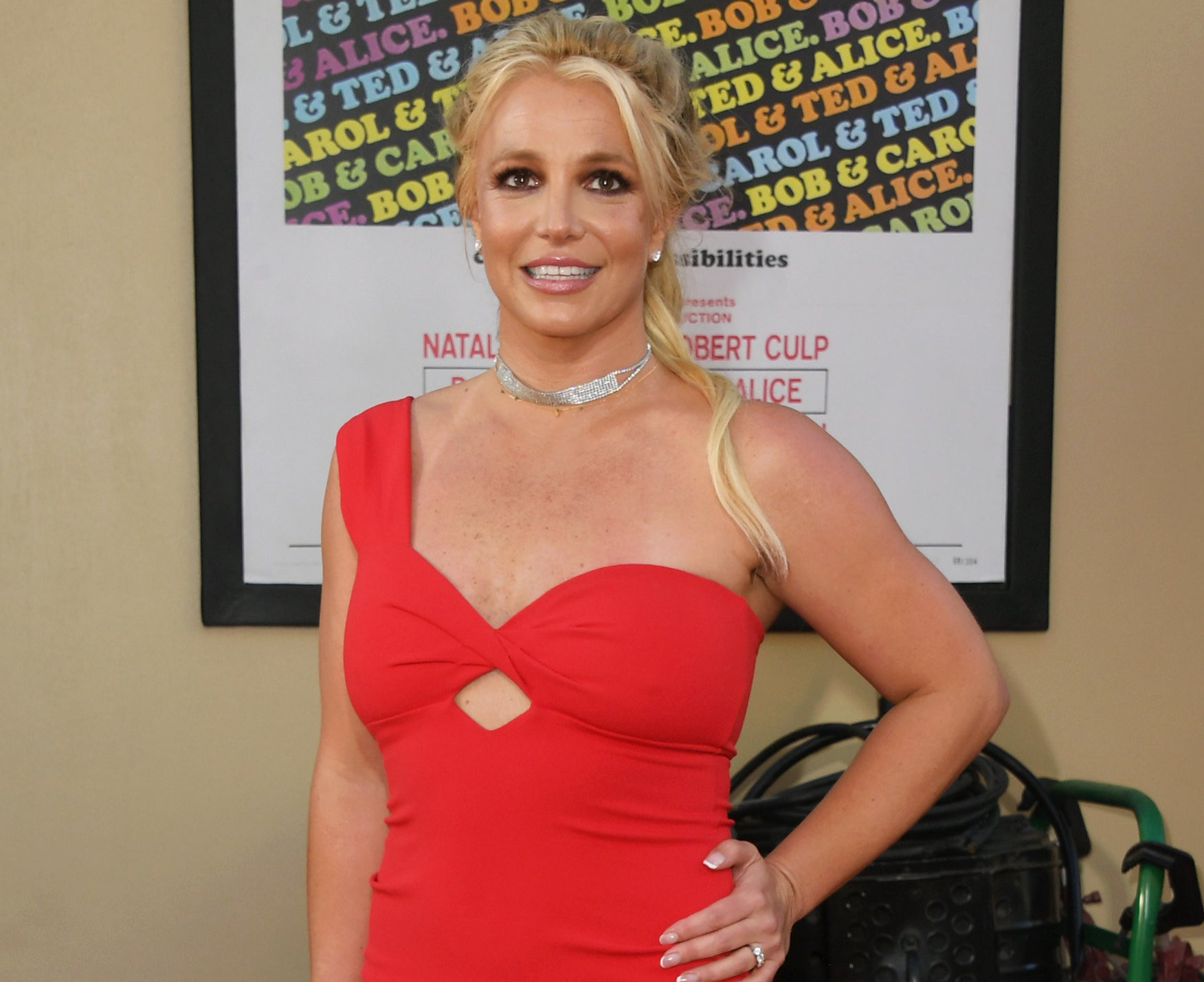 Britney wears a red one shoulder dress while attending an event