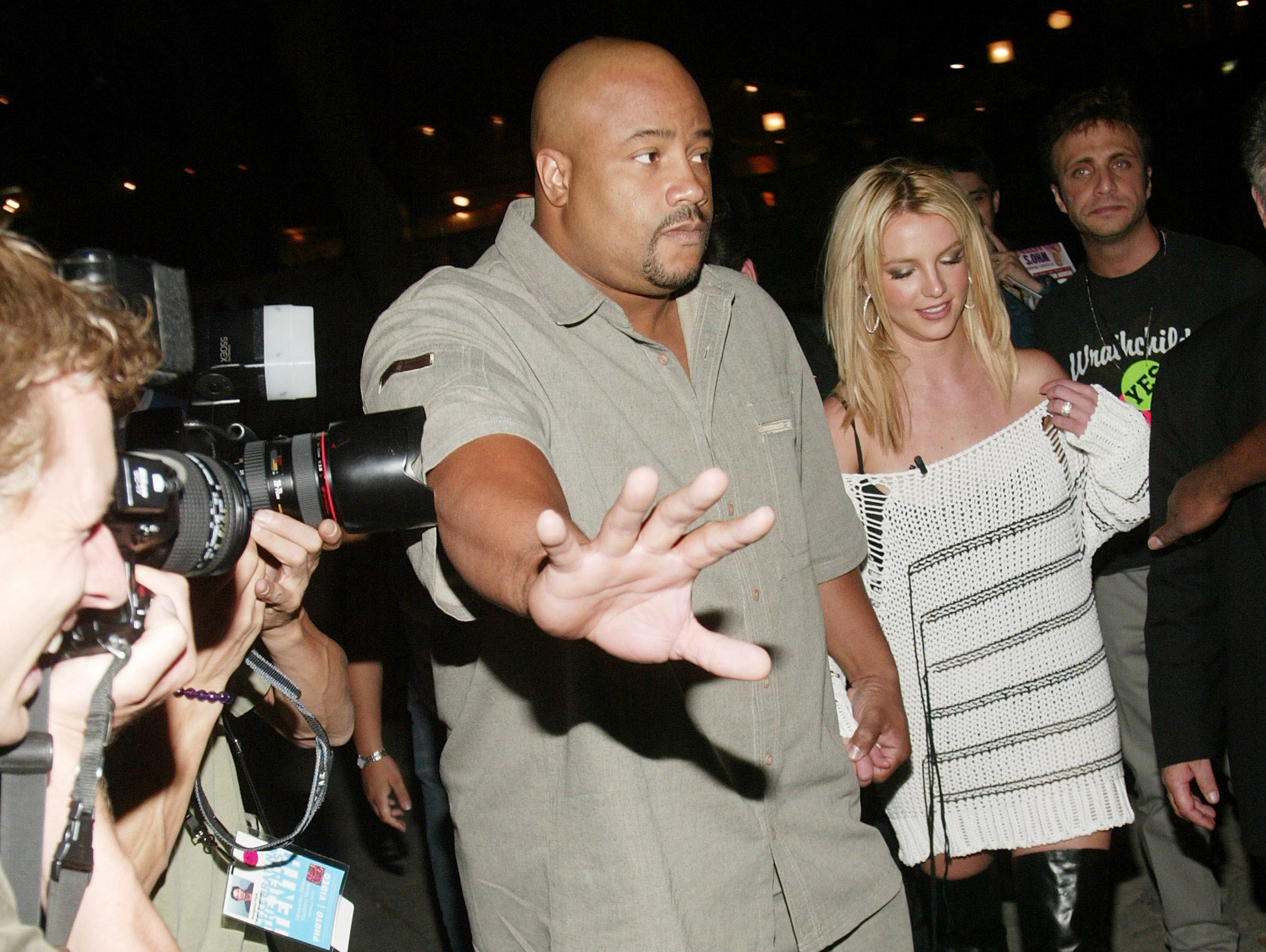 A bodyguard pushes cameras away from Britney while she walks down a street