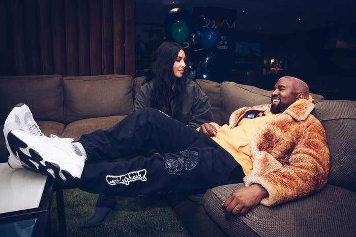 Kim Kardashian West and Kanye West siting on couches at the Travis Scott Astroworld Tour