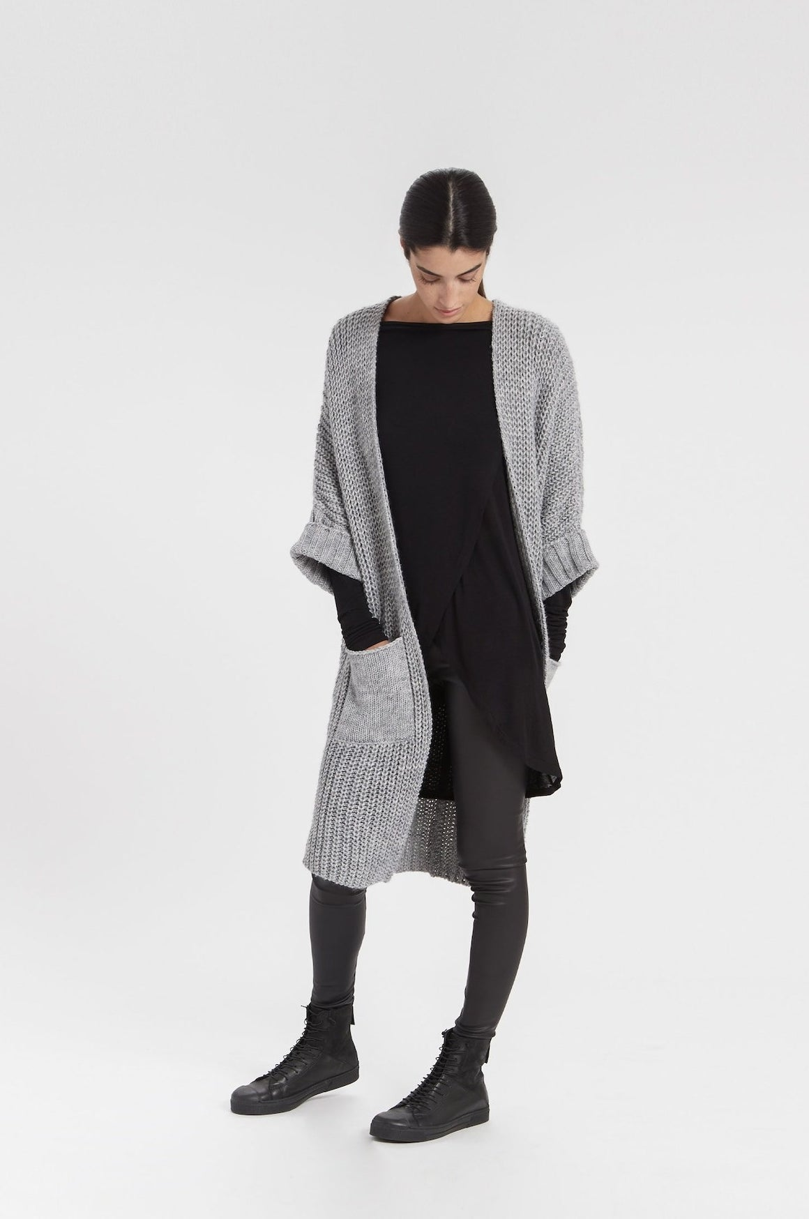 model wearing knee-length short-sleeved knit cardigan with large pockets in grey