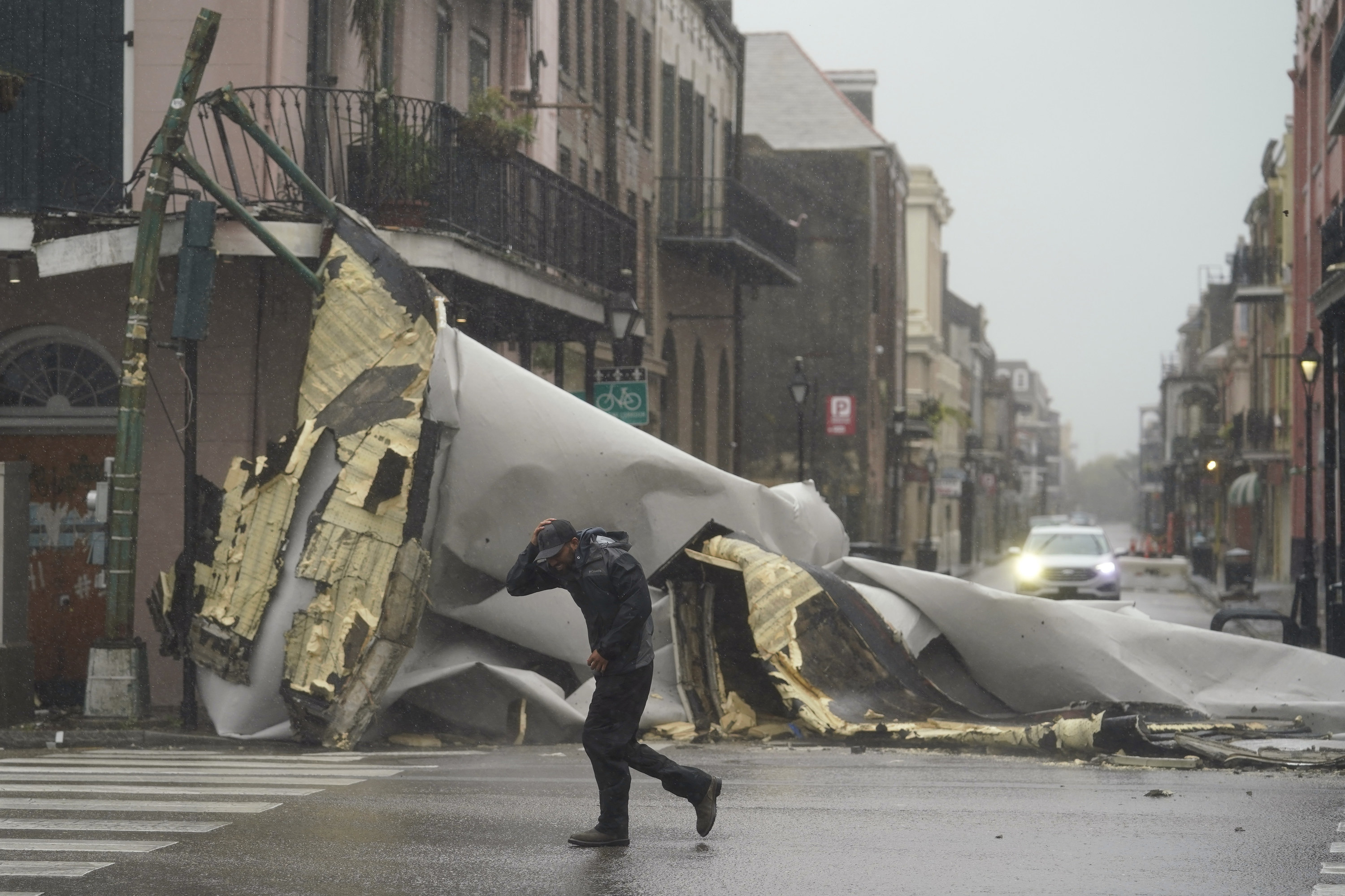 A man passes by a section of roof that was blown off of a building in the French Quarter by Hurricane Ida winds