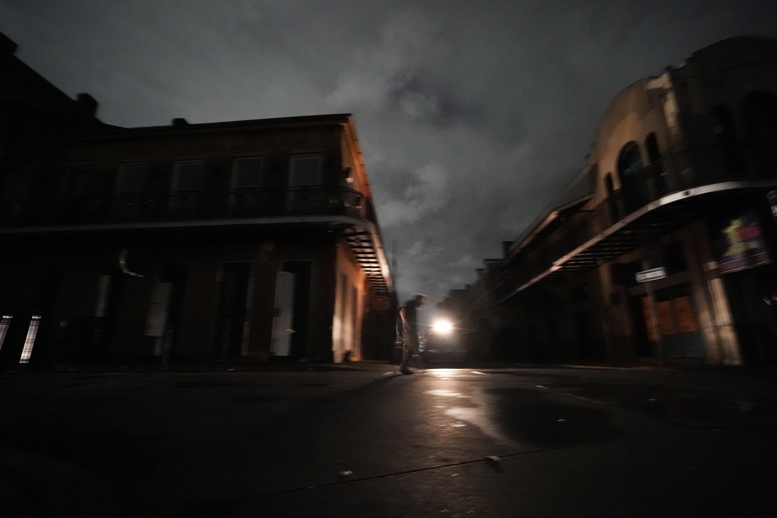 A man walks down Bourbon Street after the city lost power in the aftermath Hurricane Ida