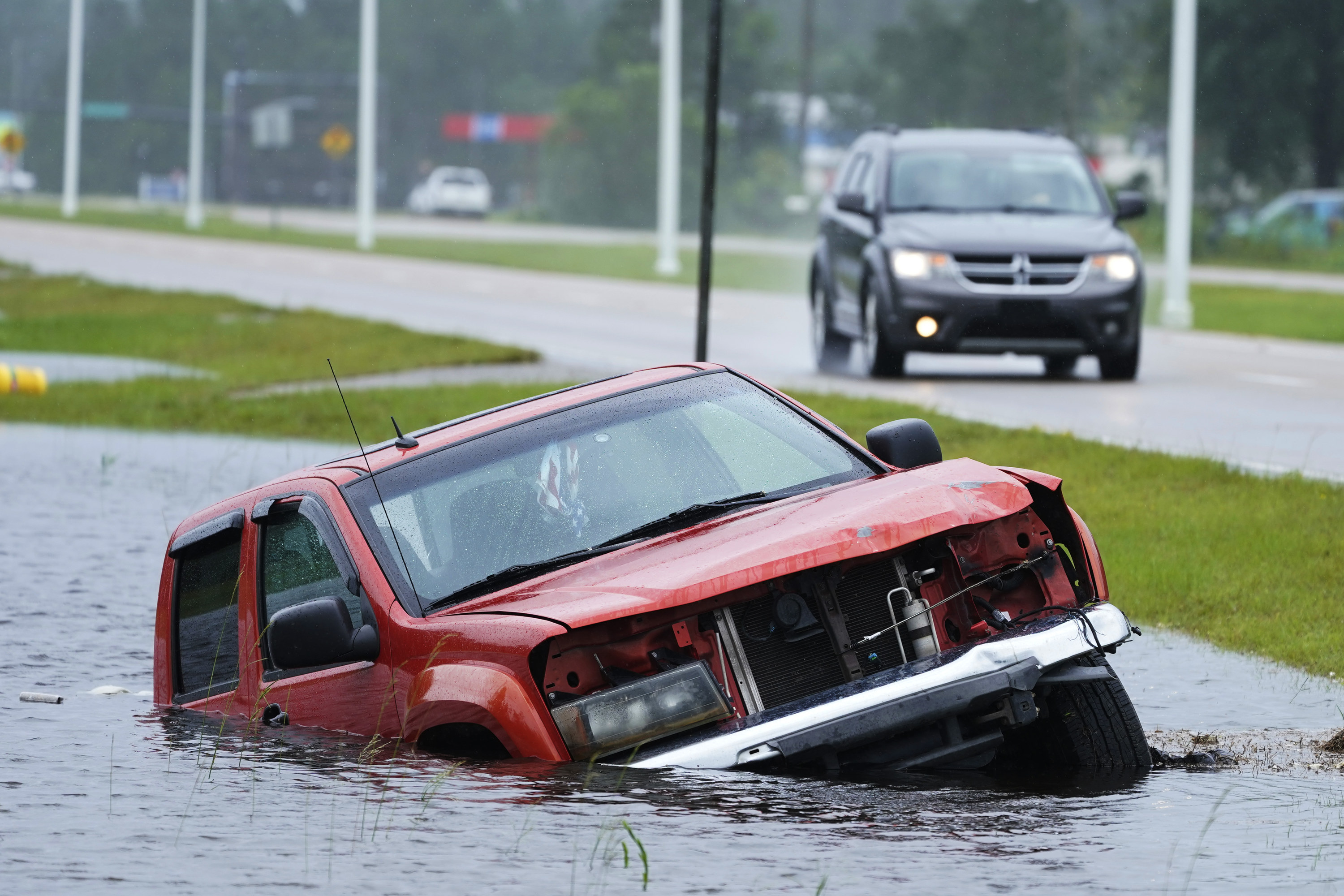 An abandoned vehicle is half submerged in a ditch next to a near-flooded highway