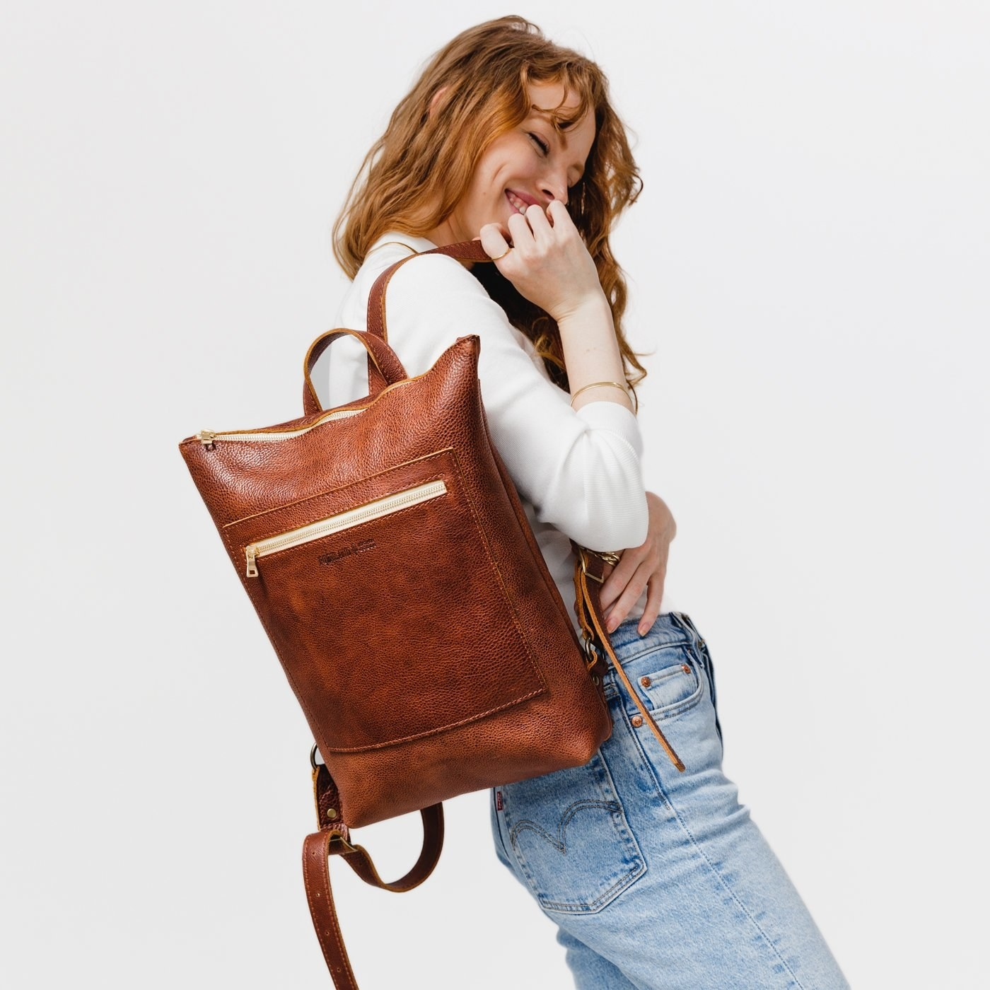 a model carrying the nutmeg leather laptop backpack over their shoulder