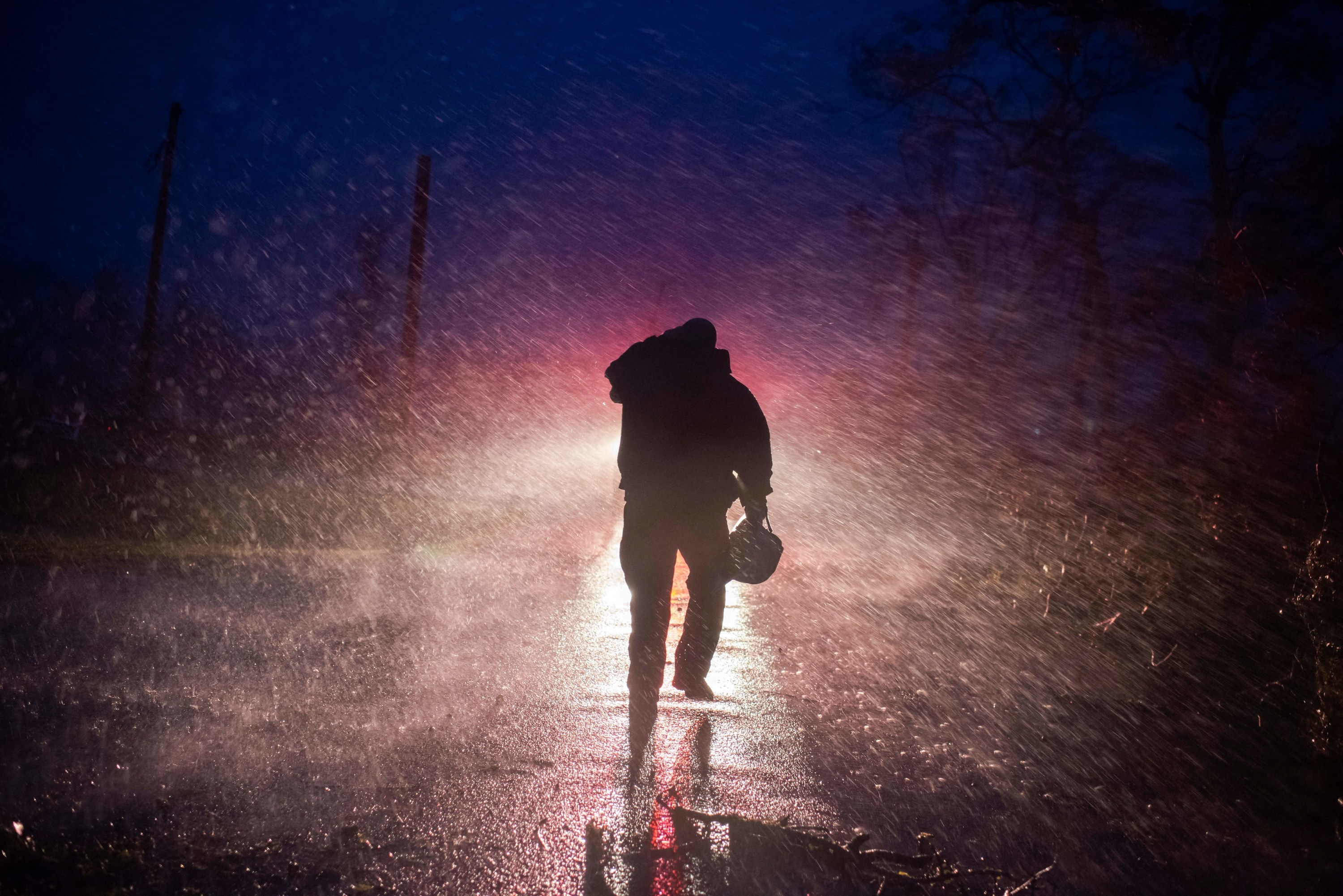 Fire chief walks back to his fire truck in the rain as firefighters cut through trees on the road in Bourg, Louisiana, as Hurricane Ida passes