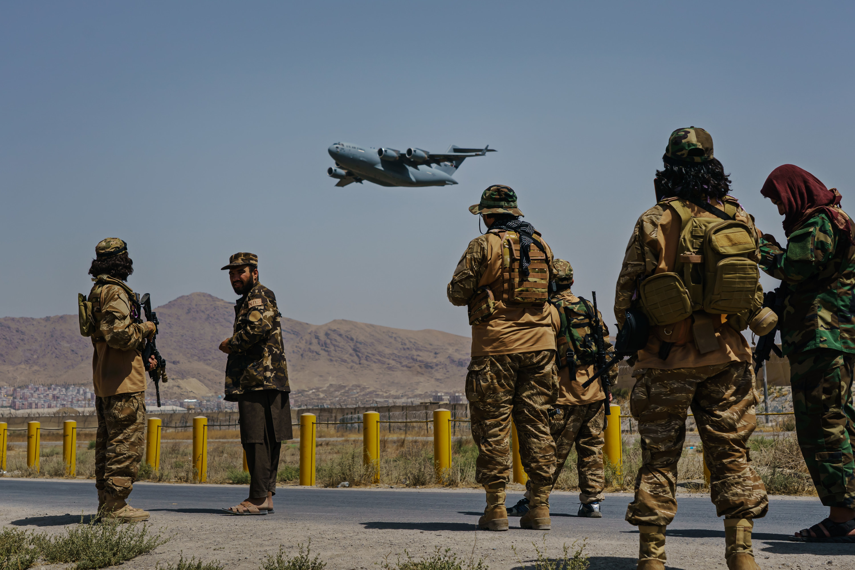 Taliban fighters stand outside Hamid Karzai International Airport as a plane flies over