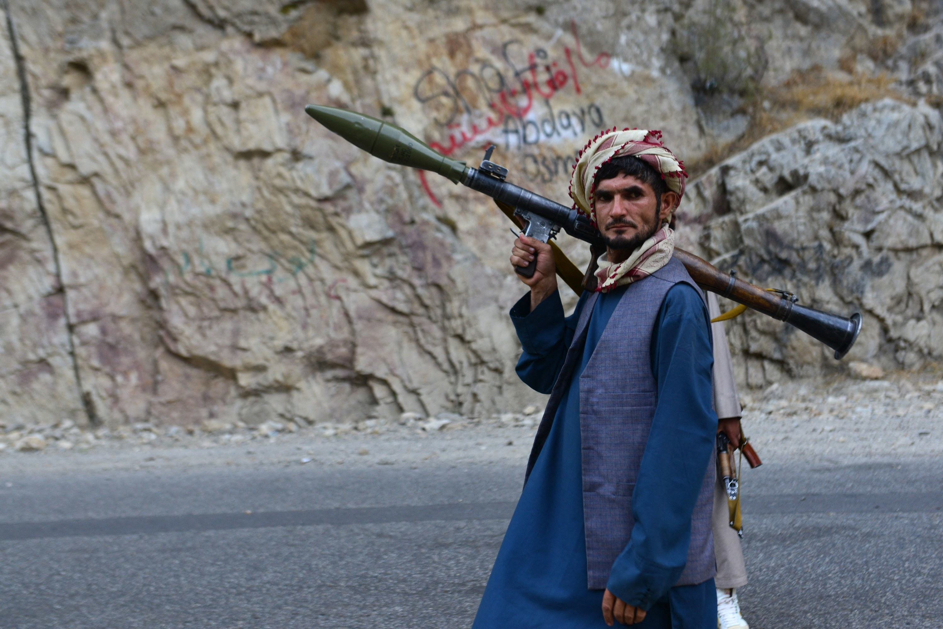 An Afghan soldier holds a gun as he patrols a remote road