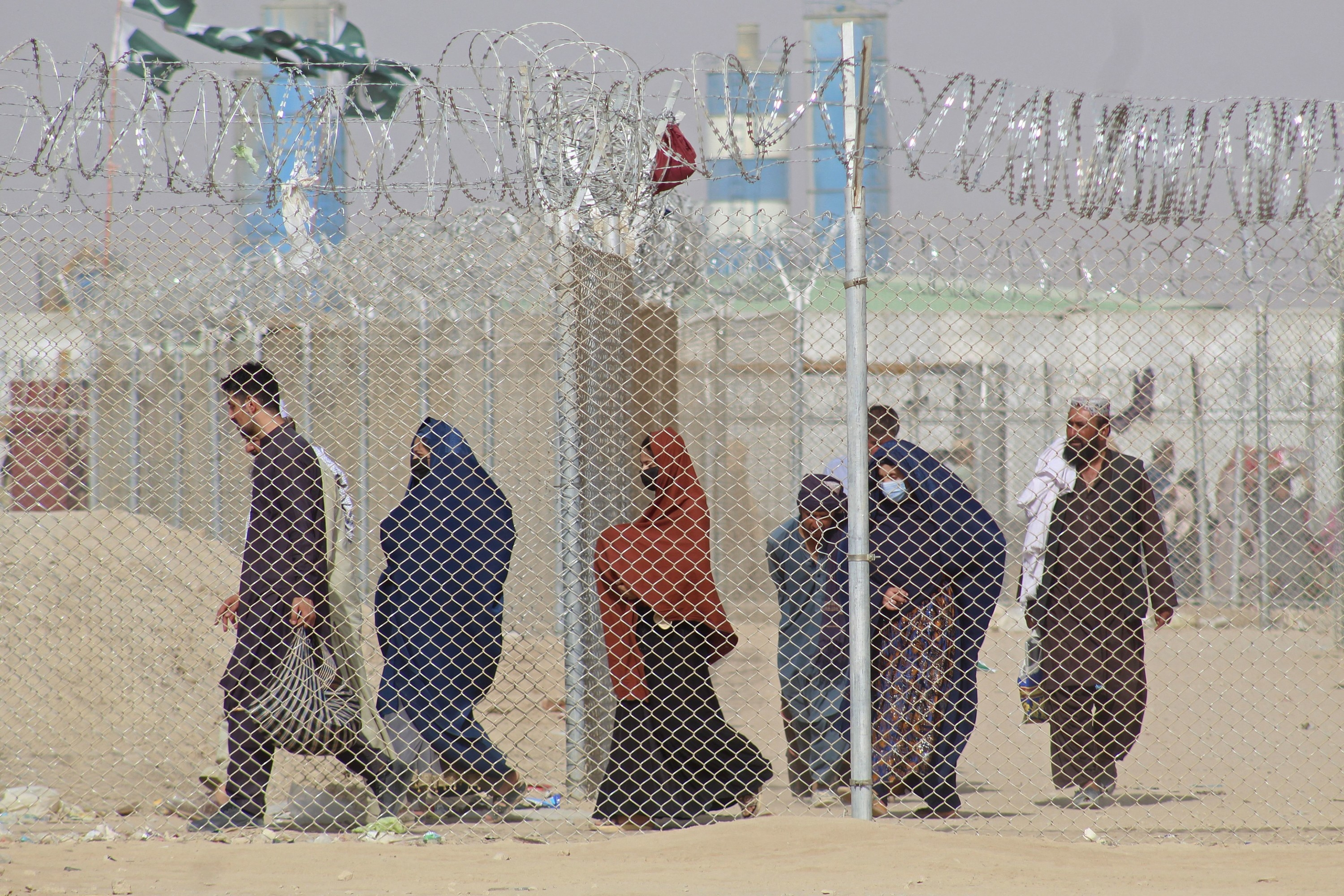 Afghan residents walk to a border station to leave for Pakistan