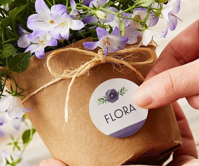 """a circle sticker that says """"flora"""" and has a purple flower on it"""