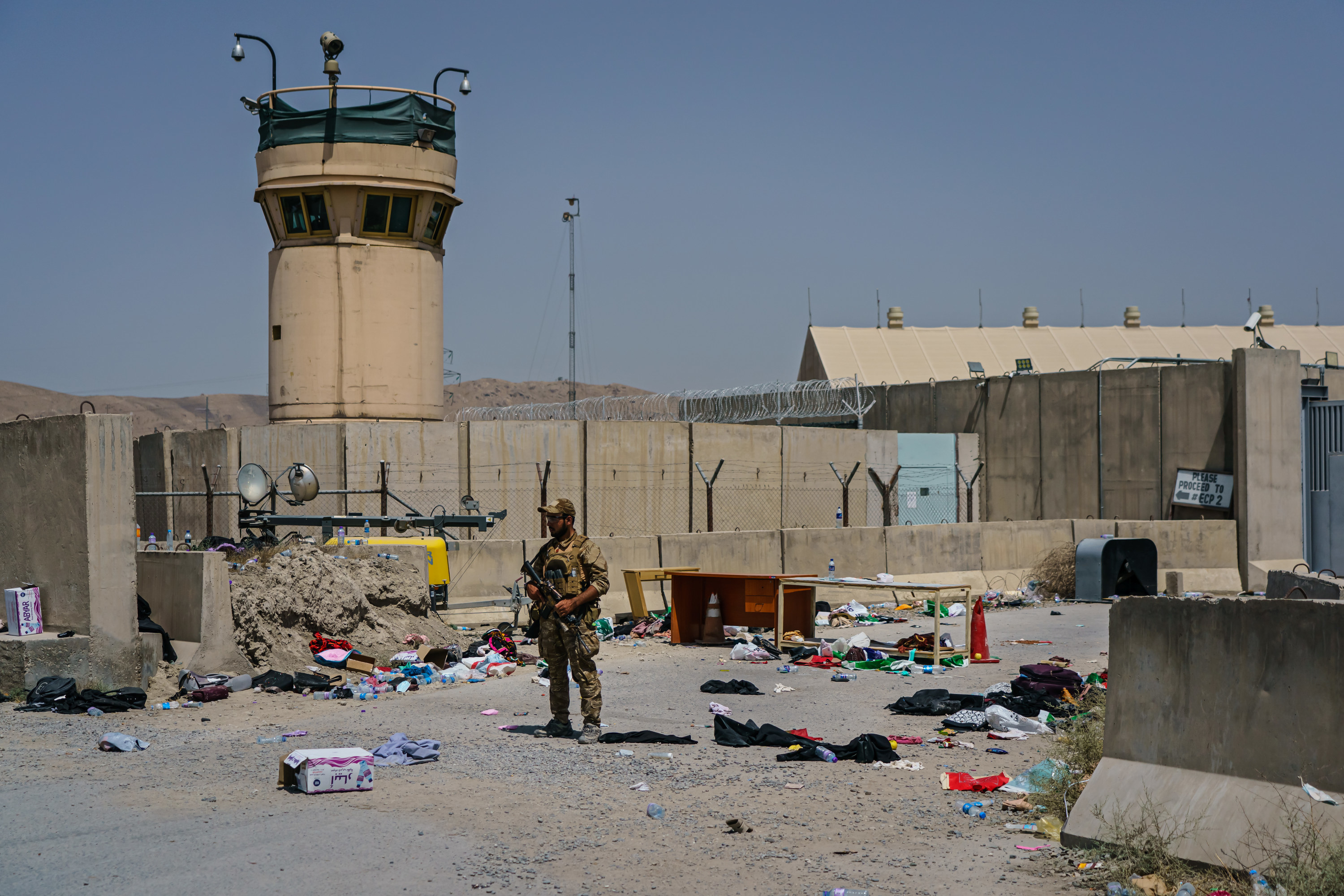 A soldier is surrounded by belongings and debris as he stands guard outside an airport