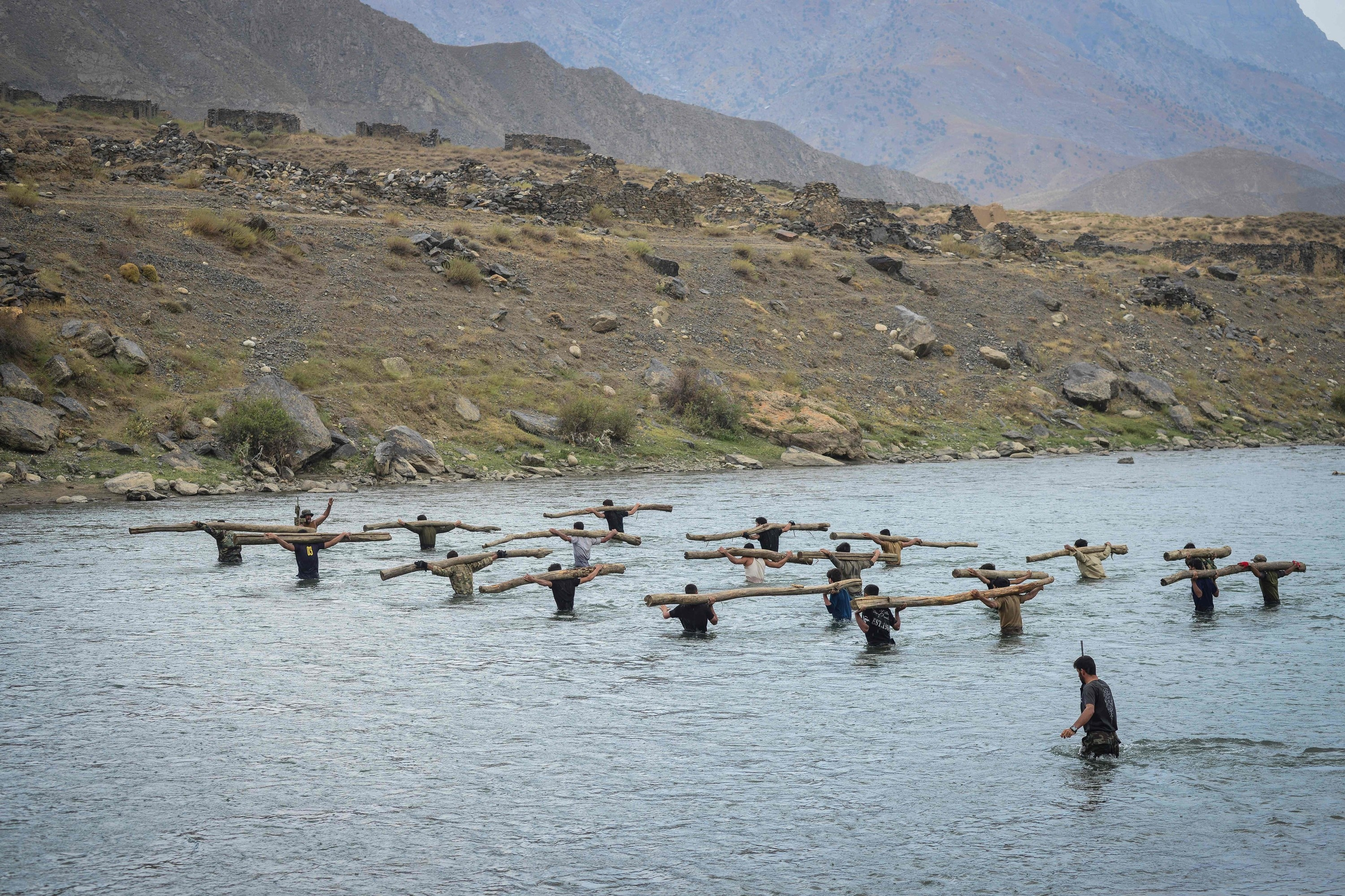 Anti-Taliban resistance soldiers train by carrying logs as they walk through water
