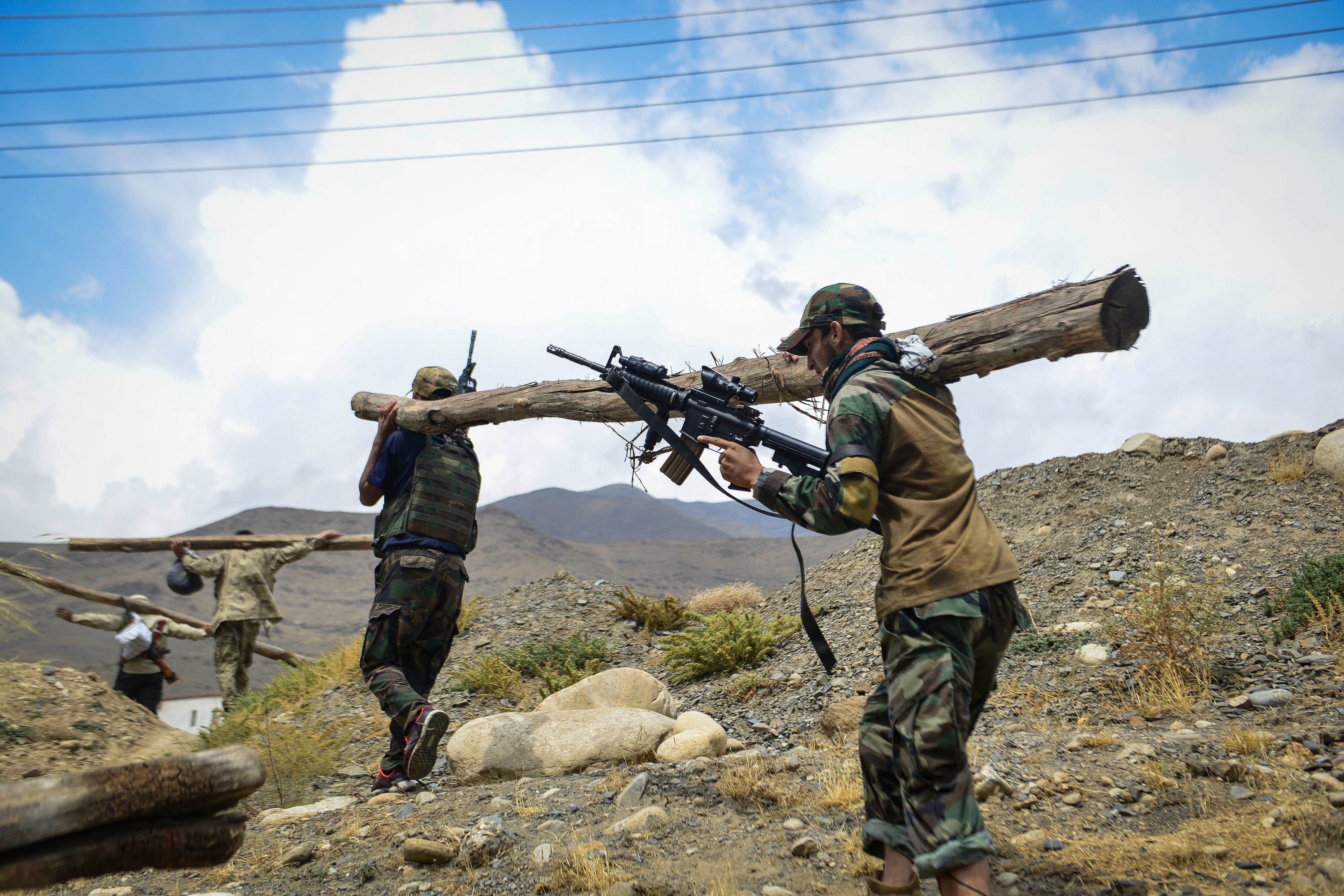 Taliban resistance soldiers hold a log and guns and participate in a training