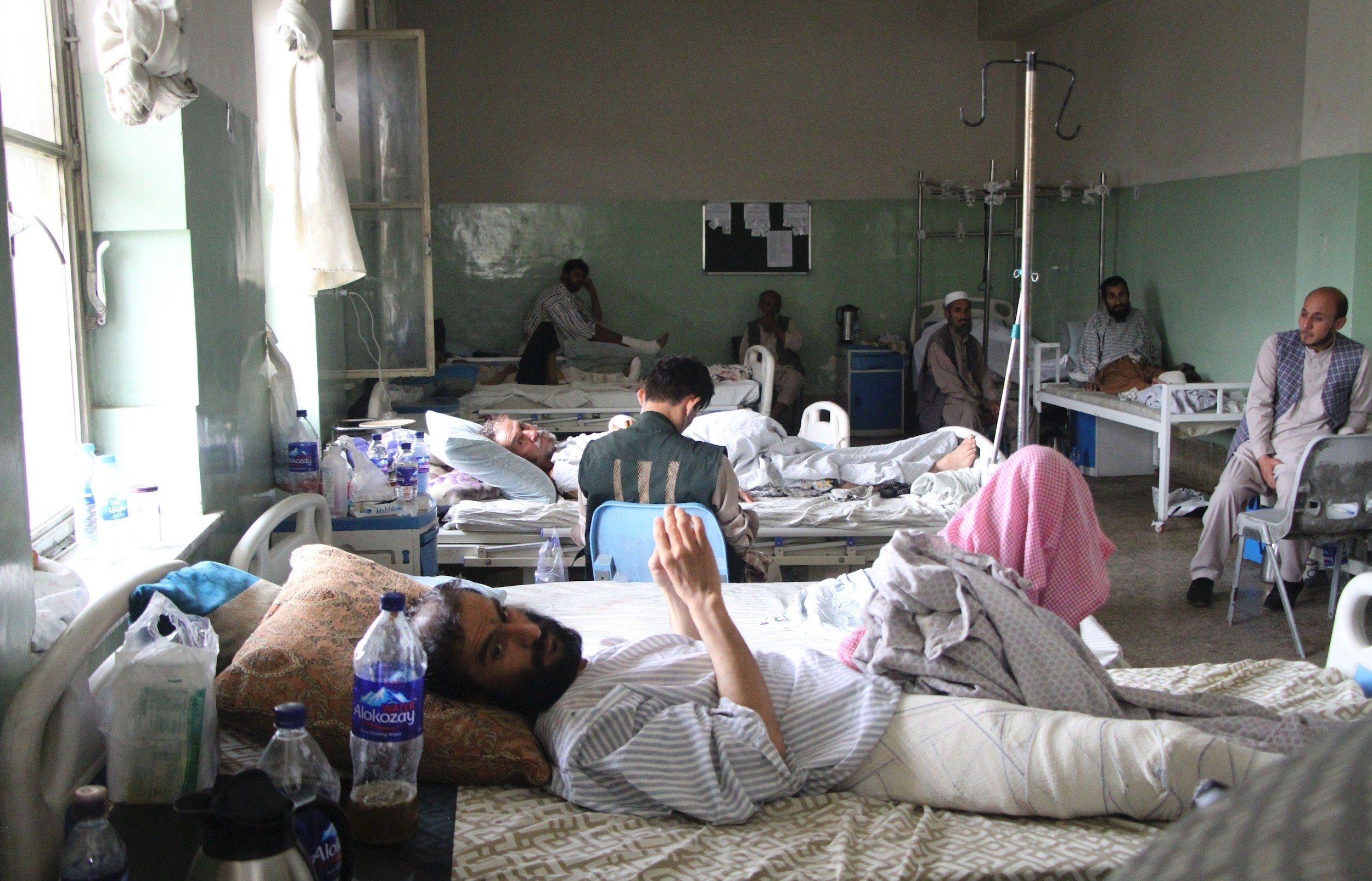 Patients at a hospital lie in bed as they heal from injuries