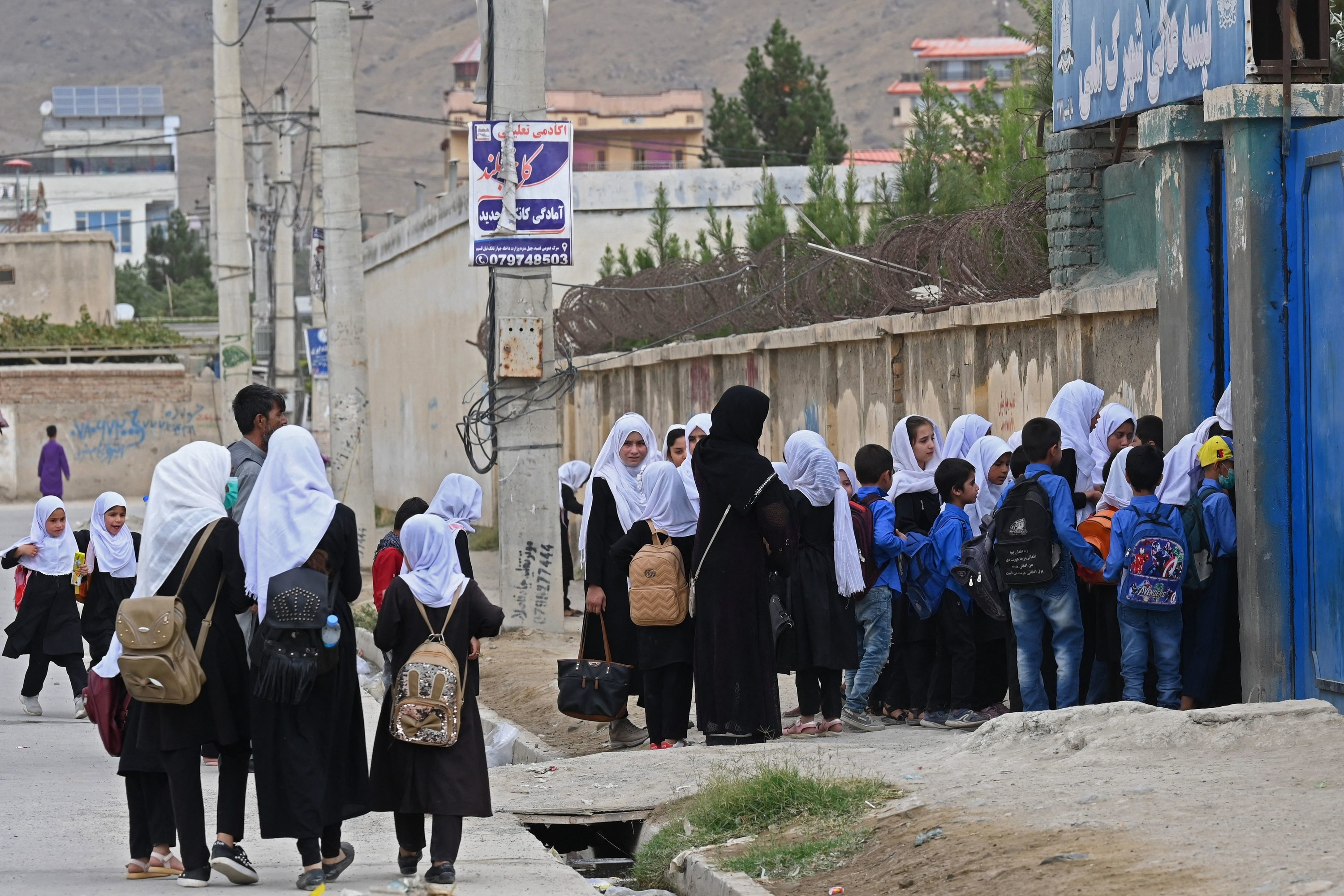 Afghan women and children are seen arriving at a school in the morning