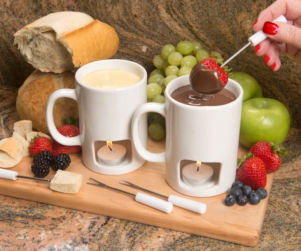 a model dipping a strawberry into a mug filled with chocolate fondue with a tea candle in the bottom compartment of the mug
