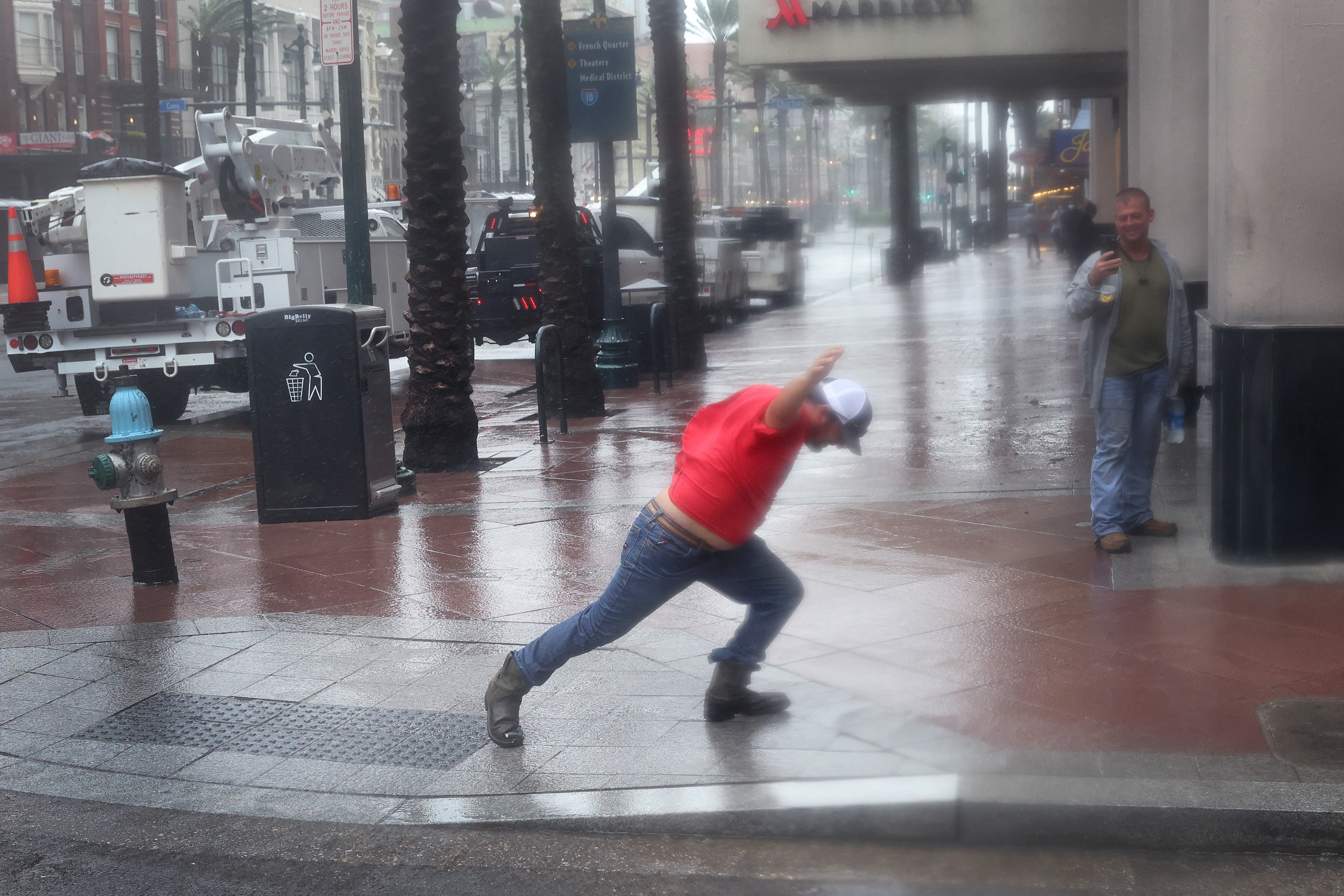 A utility worker walks against the blowing wind