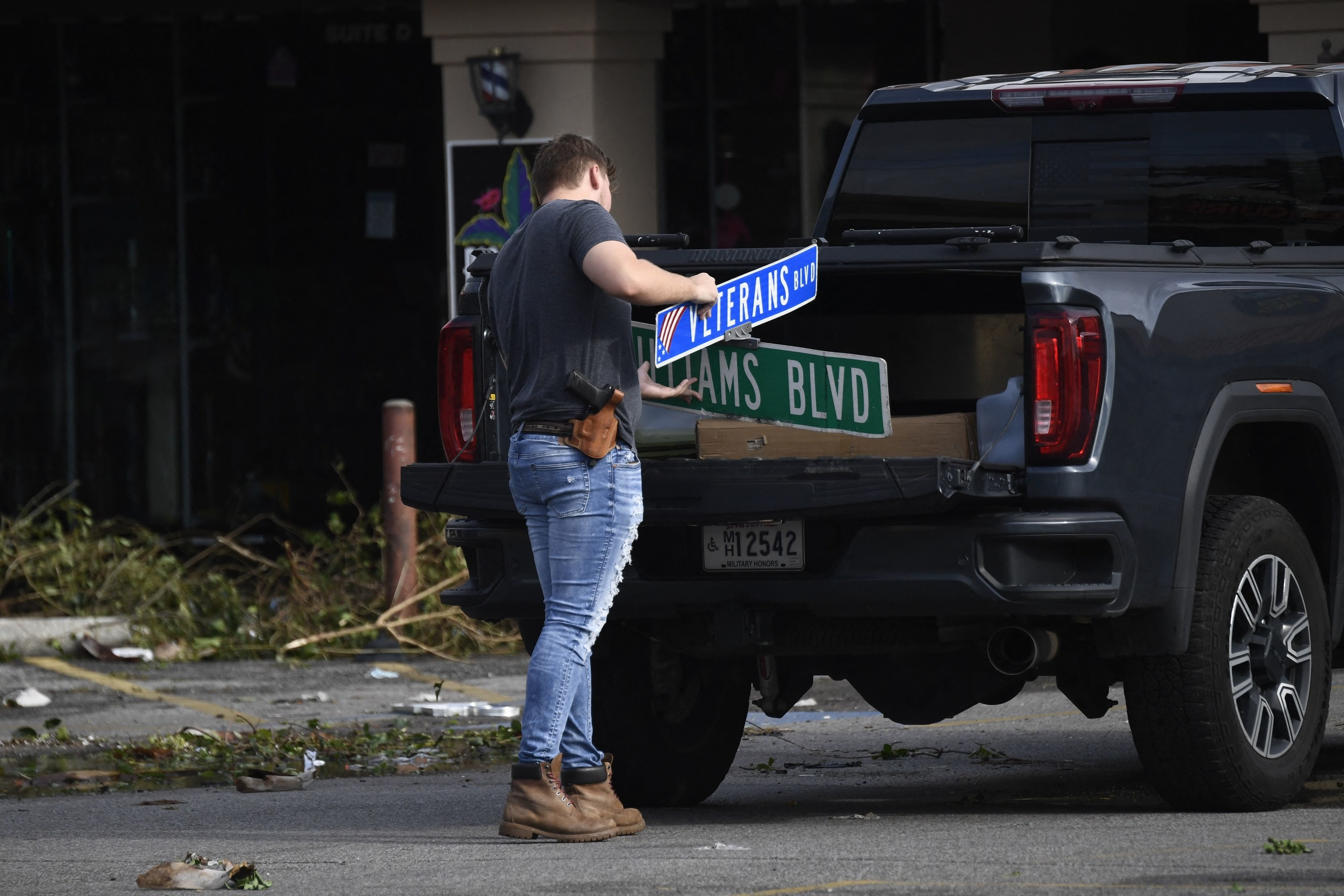 A man cleans up damaged street signs in Louisiana